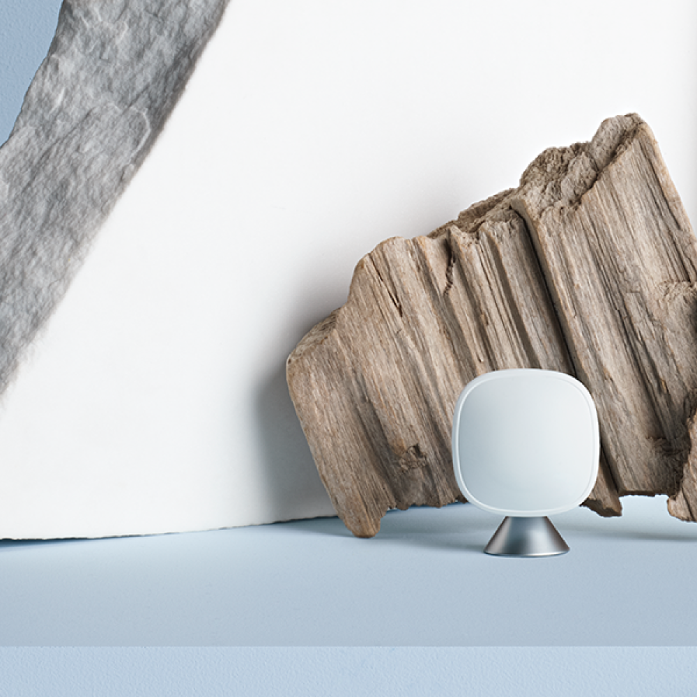Smartsensor on a powder blue background in front of a rough cut piece of wood and slab of stone.