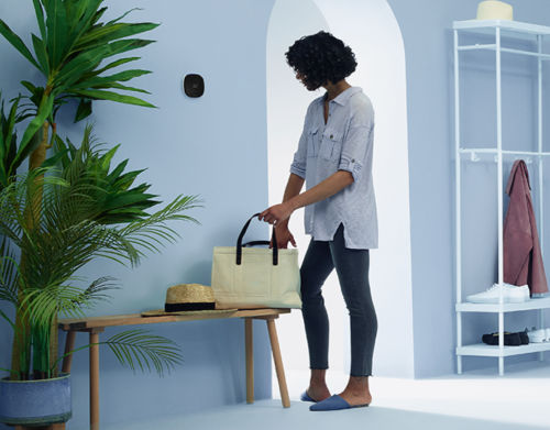 A woman gets ready to leave her home while checking her ecobee thermostat.