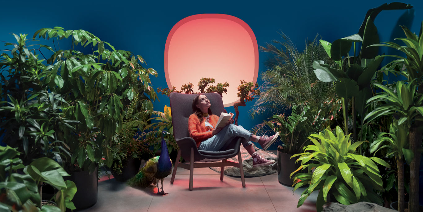 A woman sits on a chair in the middle of a plant-filled room.