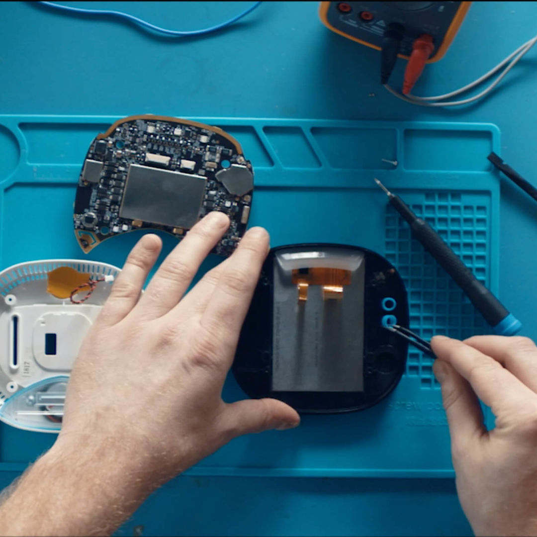 Technician  working on the machinery inside an ecobee smart thermostat.
