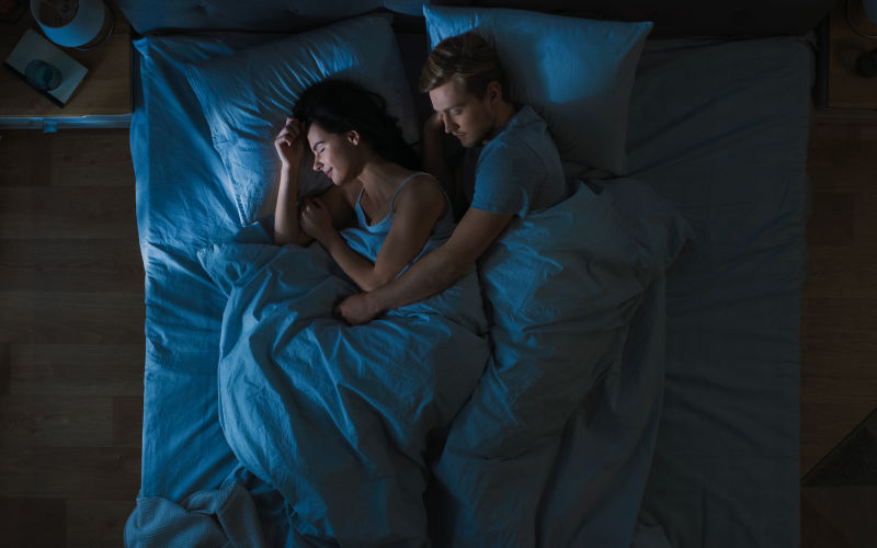 An aerial shot of a man and woman sleeping peacefully in bed.