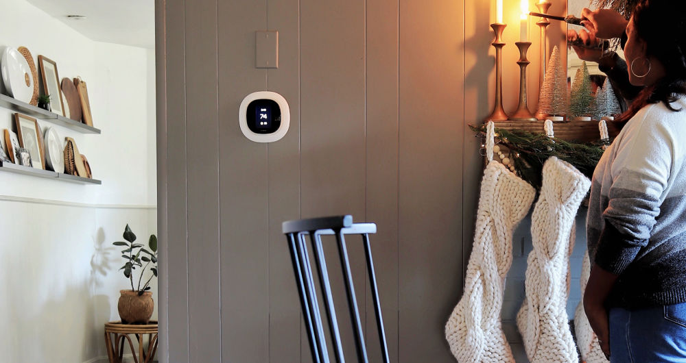 ecobee SmartThermostat with voice control display on the wall with woman lighting a candle above stockings.