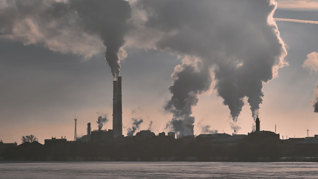 A landscape image of factory smokestacks billowing pollution.