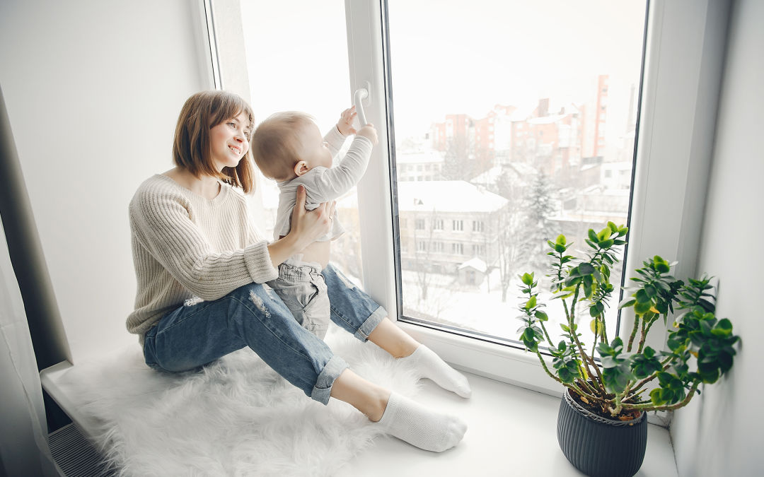 A woman with a baby sit in front of a large, clean window.