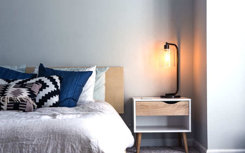Warm temperature Edison bulb lamp sitting on modern bed side table casts a warm glow against the surrounding corner walls.