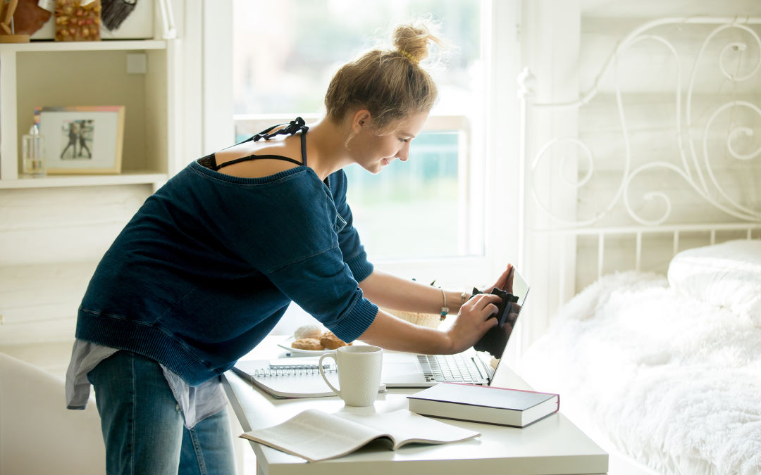 Teenager in blue shirt sets up her bedroom office desk on a sunny morning.