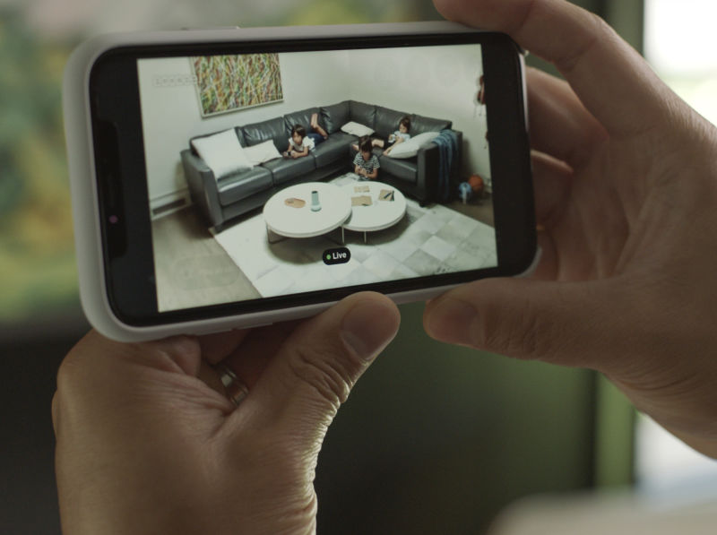 View of a remote-monitored living room through a phone screen.