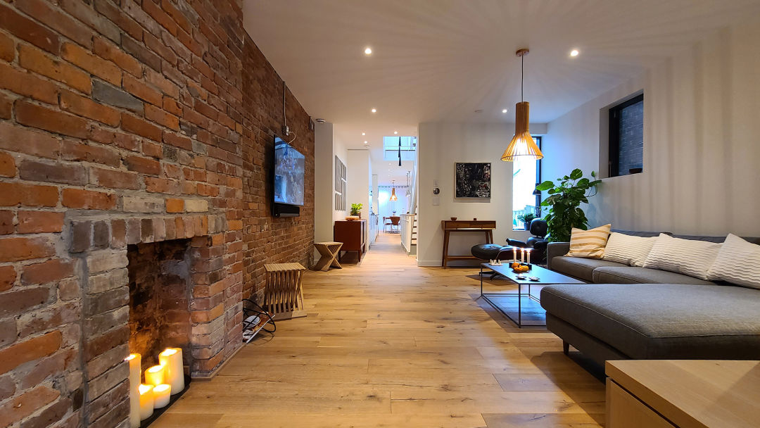 Perfectly conceived Danish modern open-concept living room with l-shaped couch, exposed brick wall, pot lighting, pendant light centerpiece on hardwood floor.