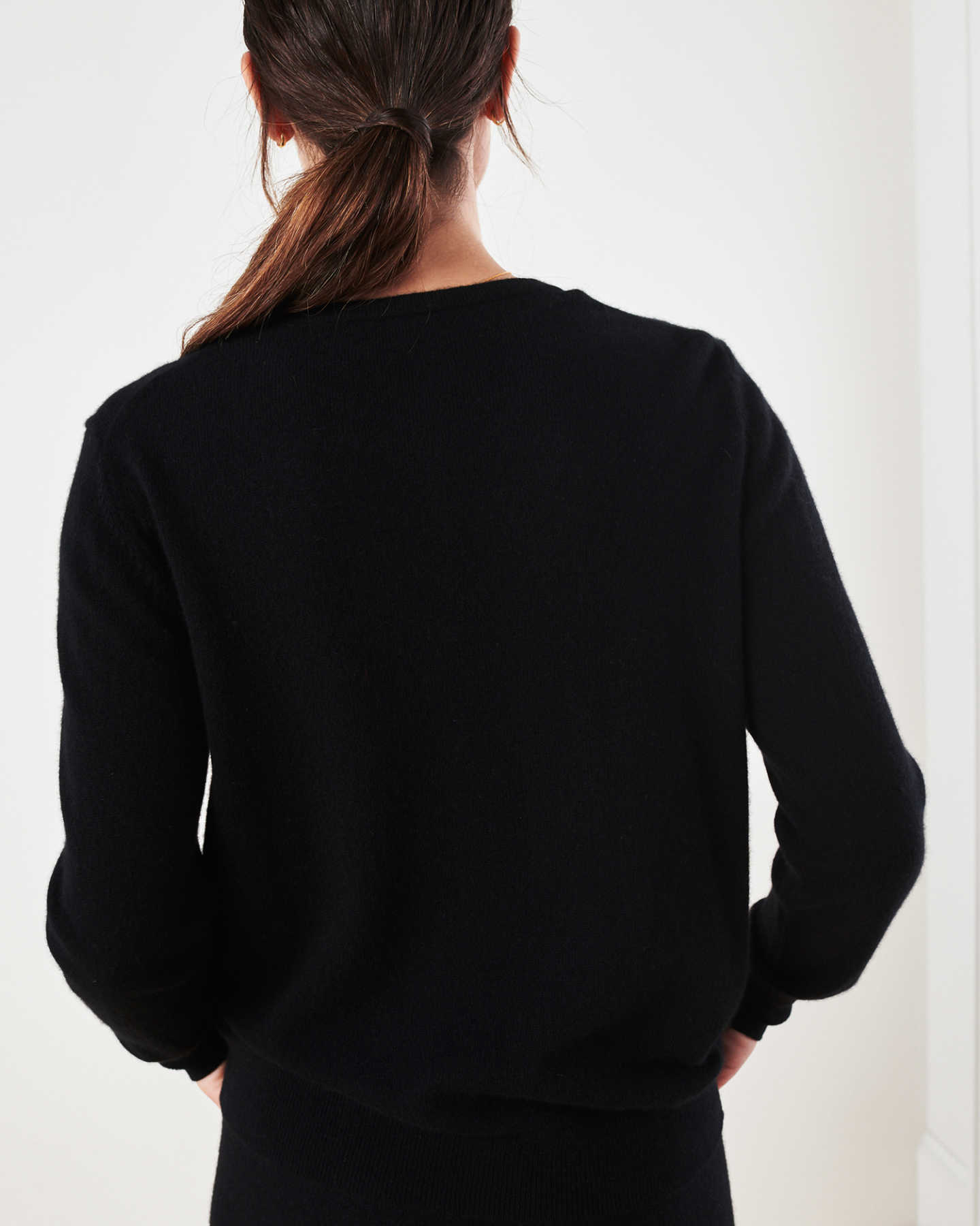 Woman wearing black cashmere cardigan sweater and black cashmere sweatpants back