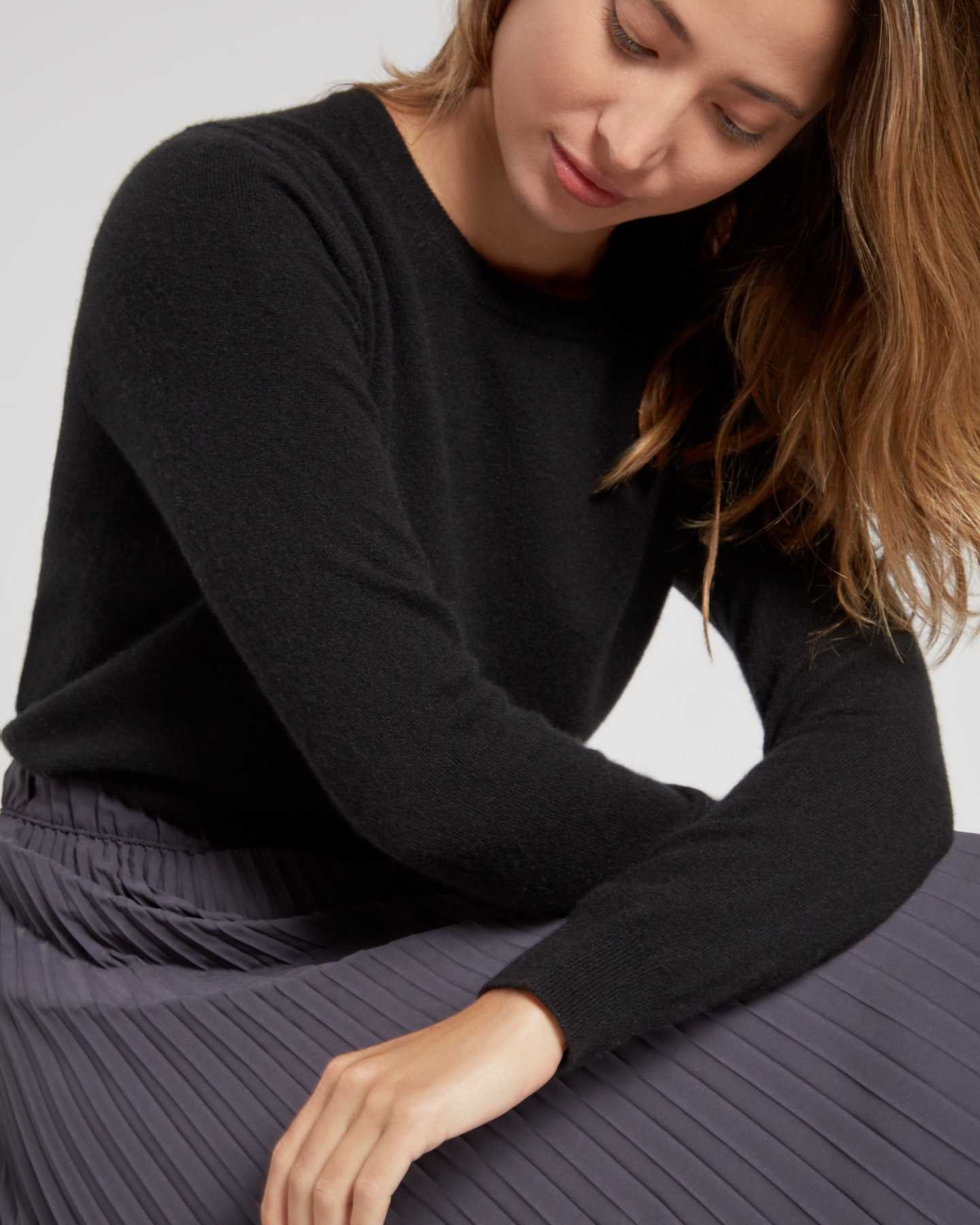 black cashmere sweater women sitting