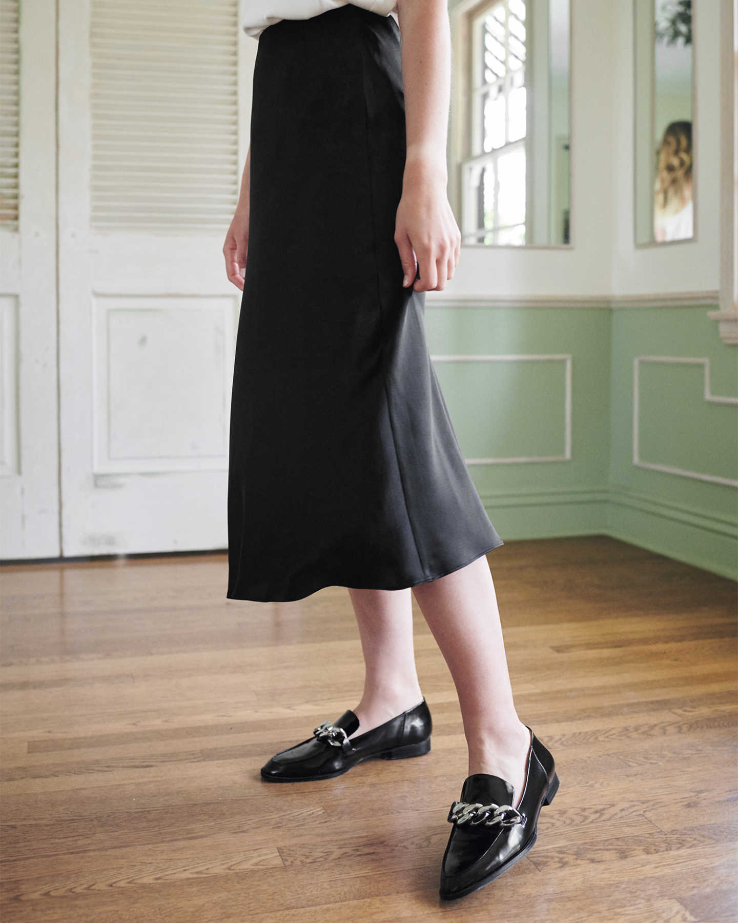 Woman wearing black silk skirt from side