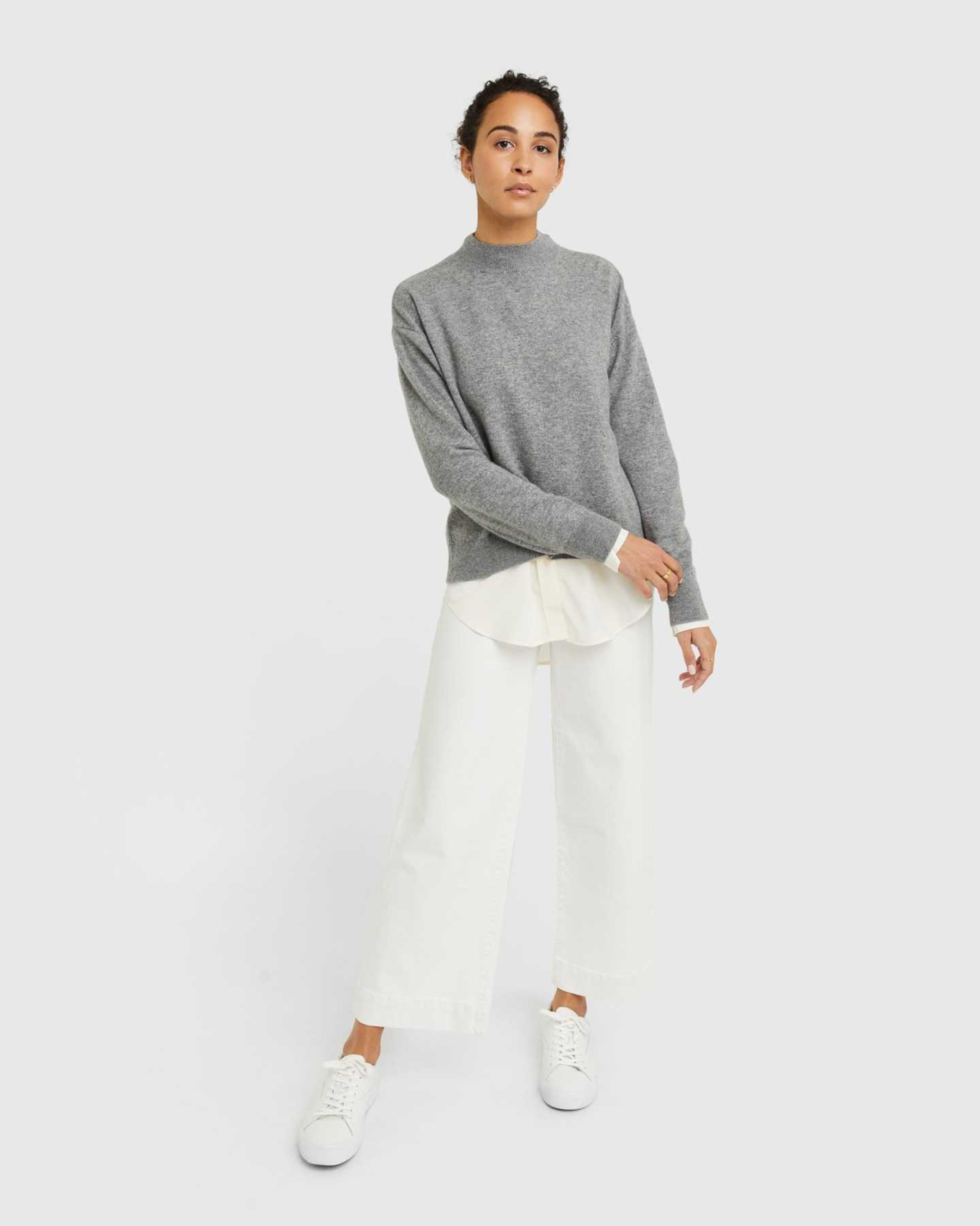 Woman wearing grey cashmere mockneck sweater standing