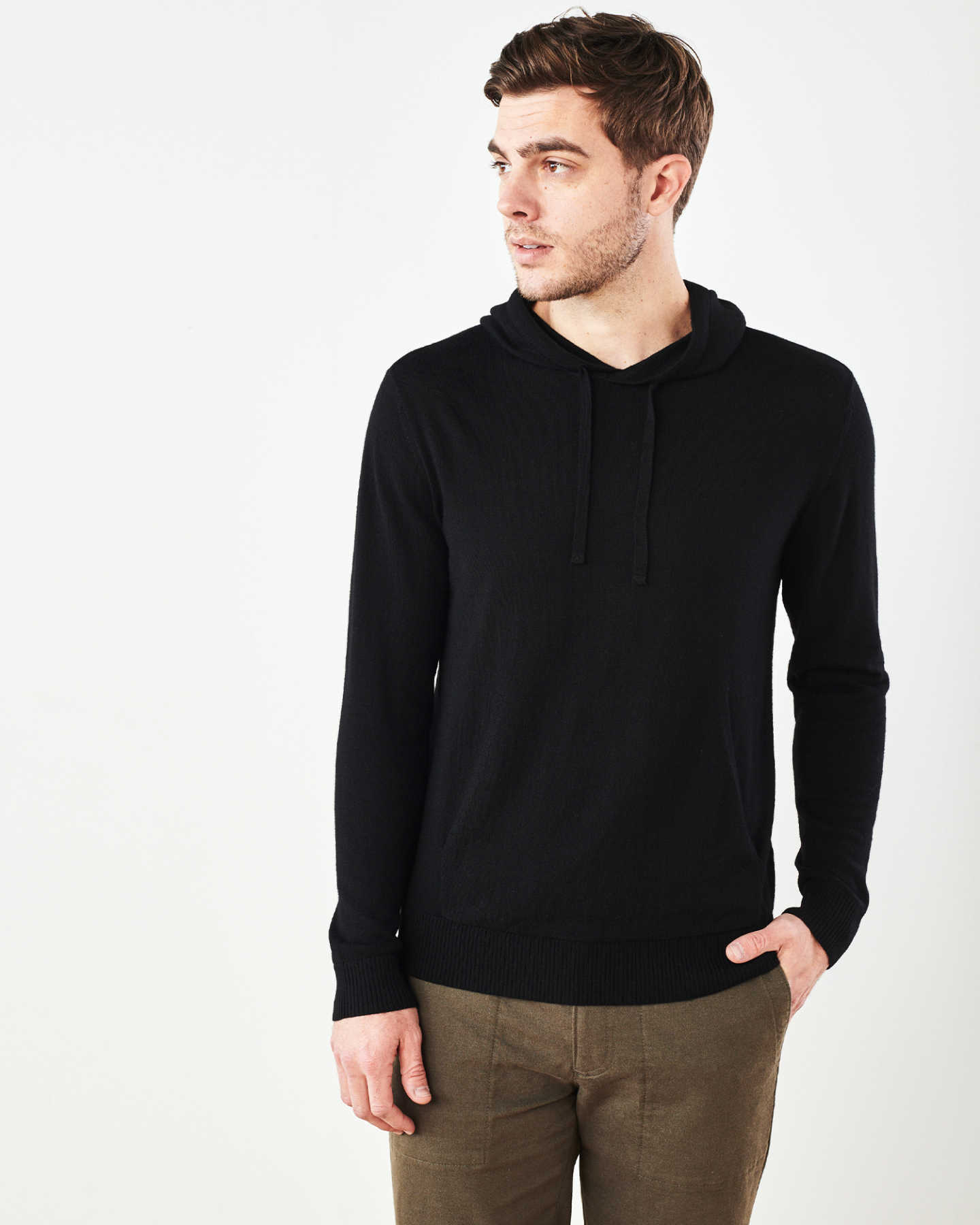 Man wearing merino wool hoodie in black looking right