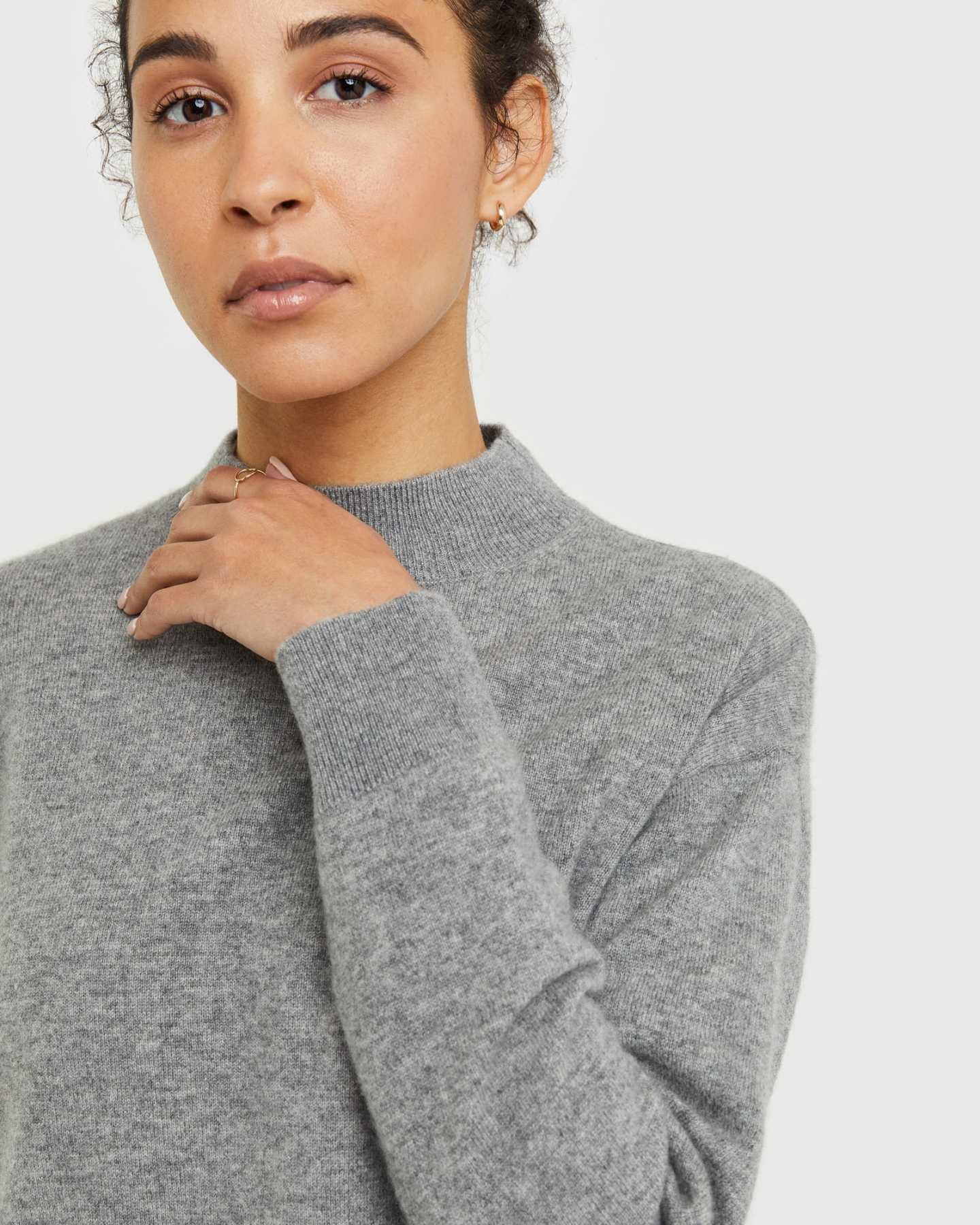 Woman wearing grey cashmere mockneck sweater zoomed in