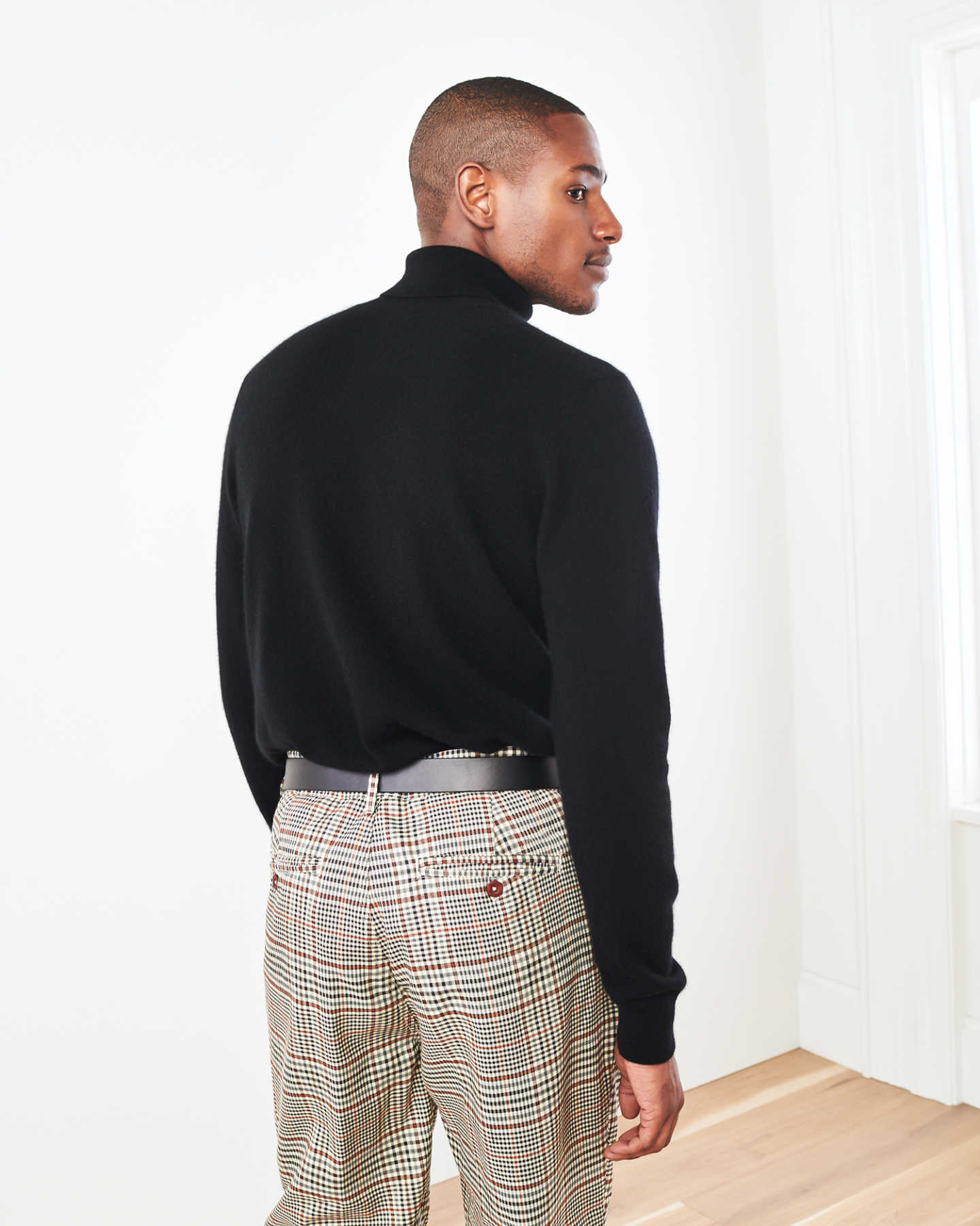 Man wearing men's black cashmere turtleneck sweater from behind