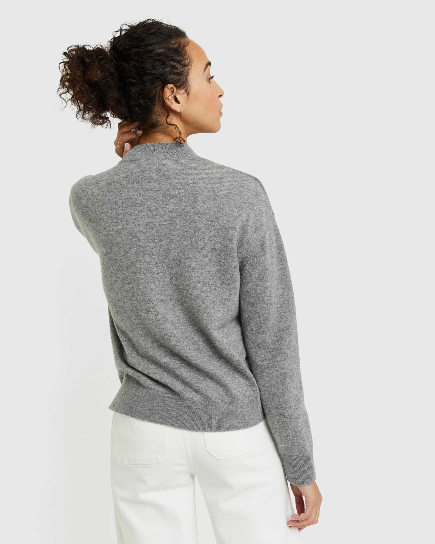 Woman wearing grey cashmere mockneck sweater toucing her neck