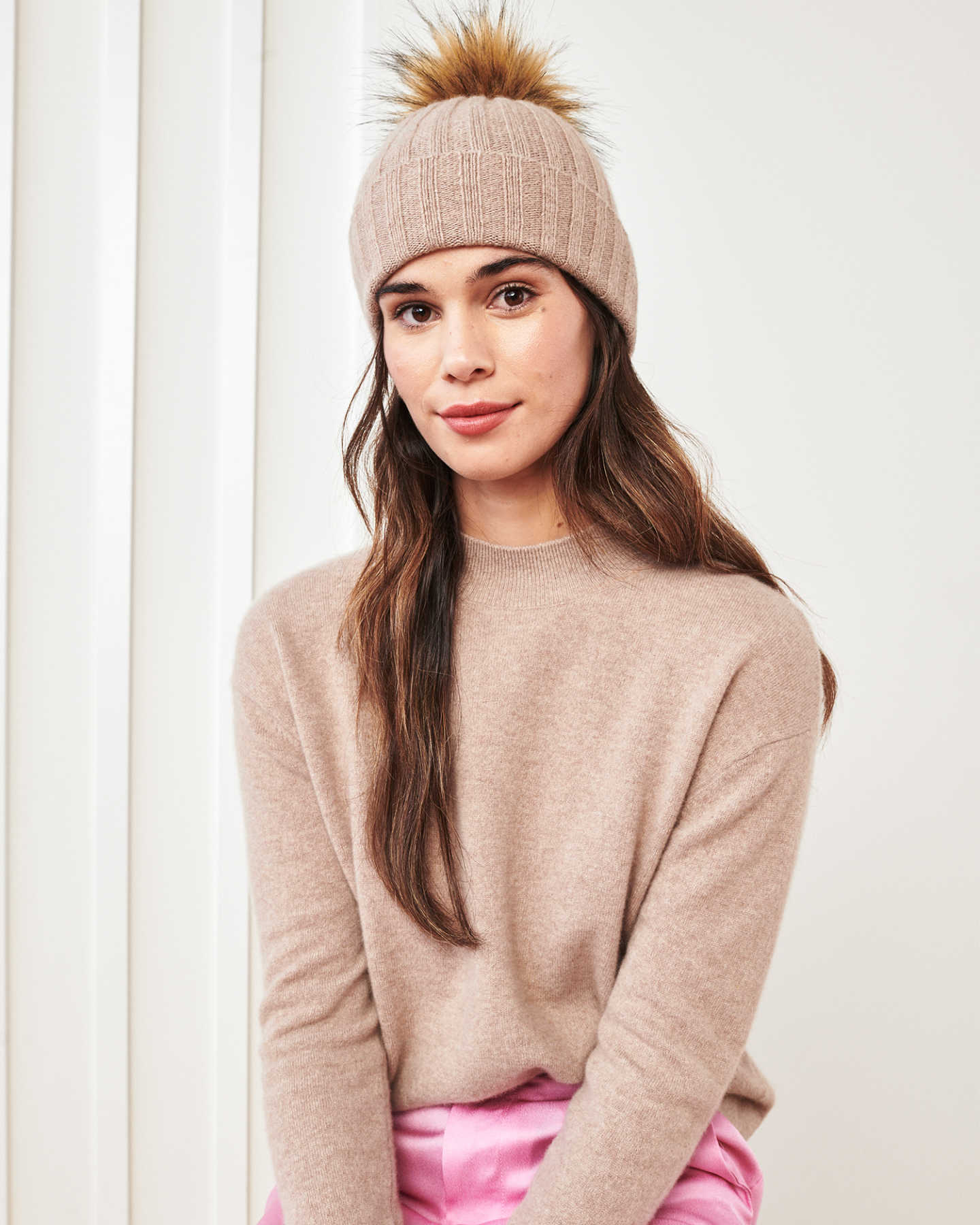 Woman wearing a cashmere pom pom beanie in oatmeal and matching cashmere mockneck sweater