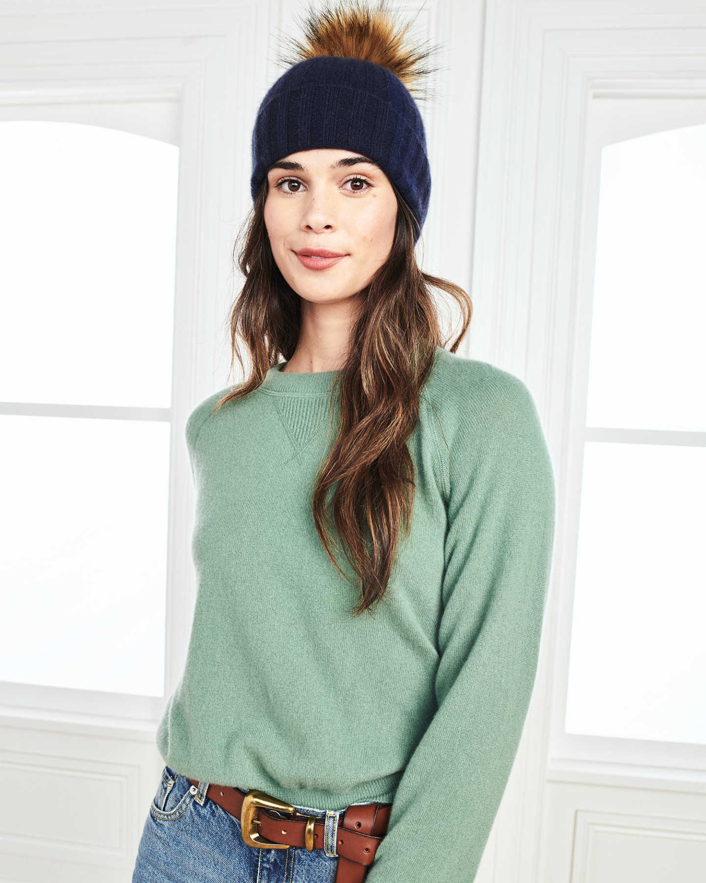 Woman wearing a womens beanie with pom in navy and matching cashmere sweatshirt in green by window