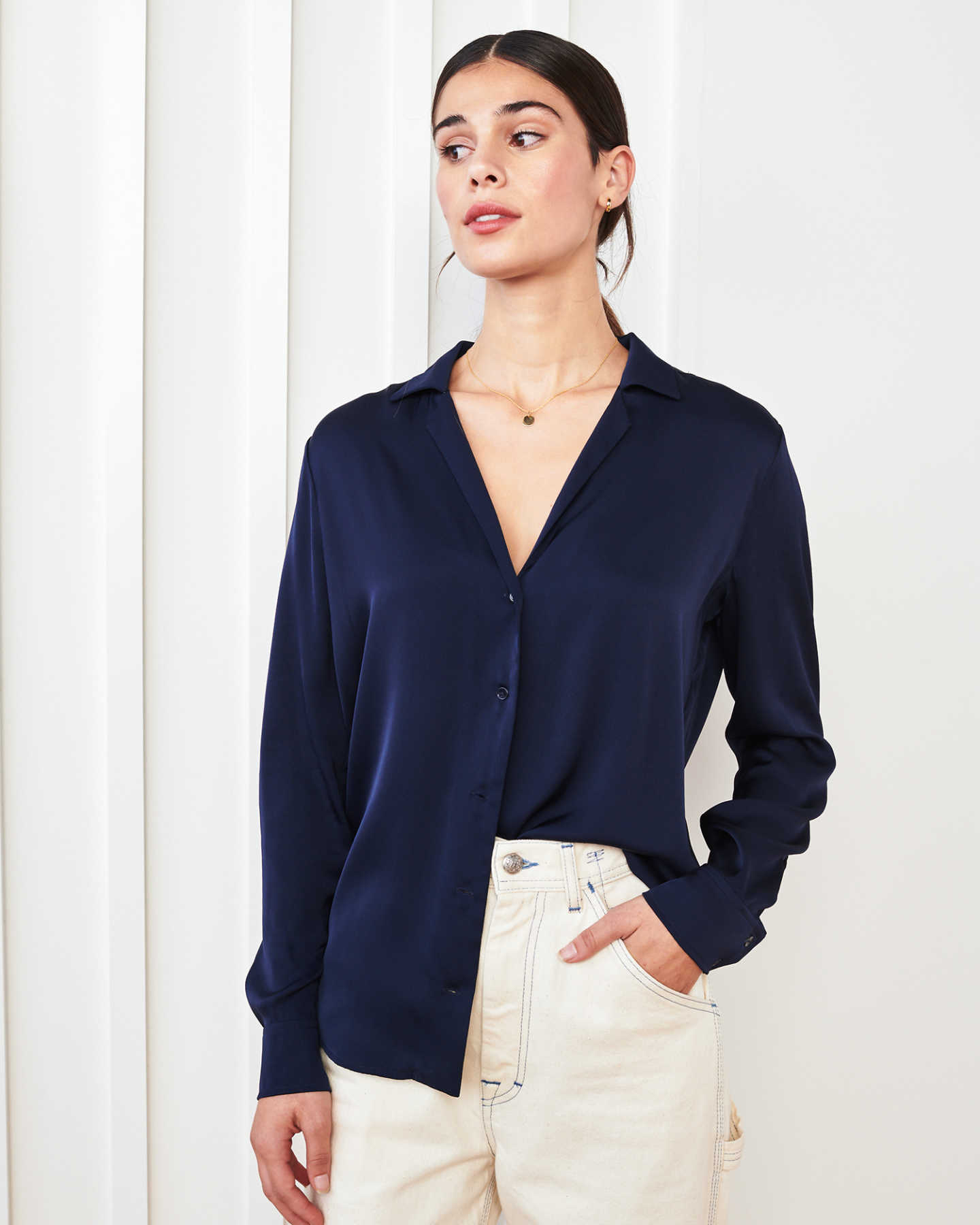 woman wearing silk notch collar blouse in navy looking to side