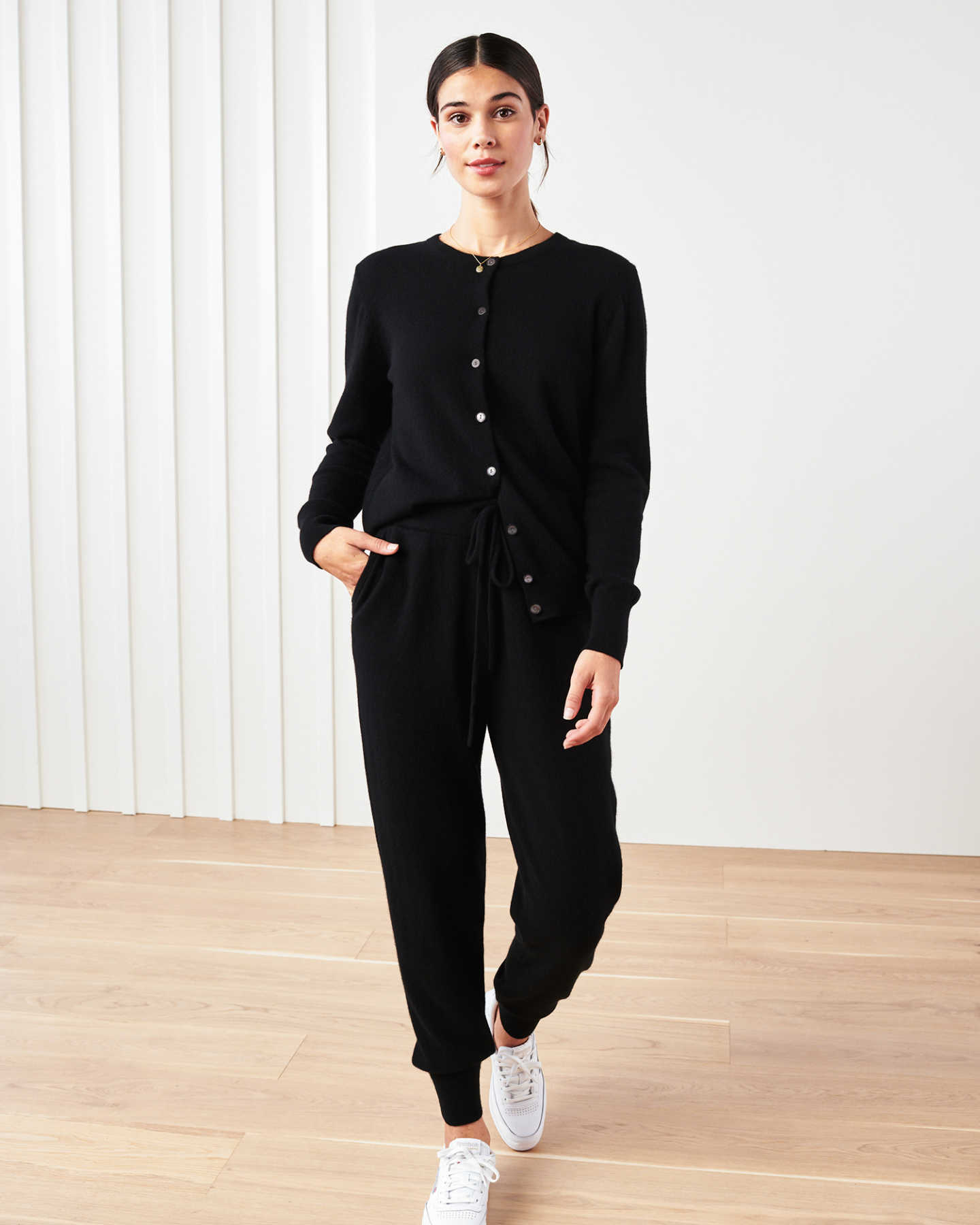 Woman wearing black cashmere cardigan sweater and black cashmere sweatpants posing