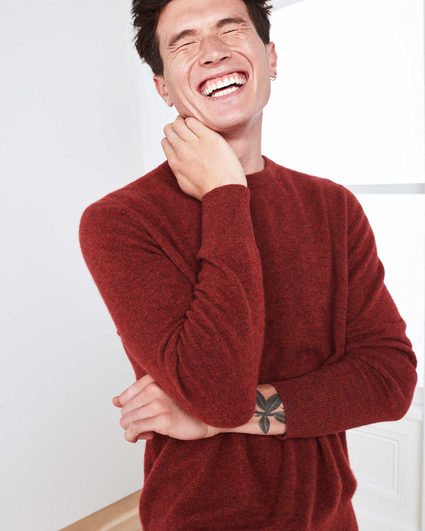 Man wearing red men's cashmere sweater laughing