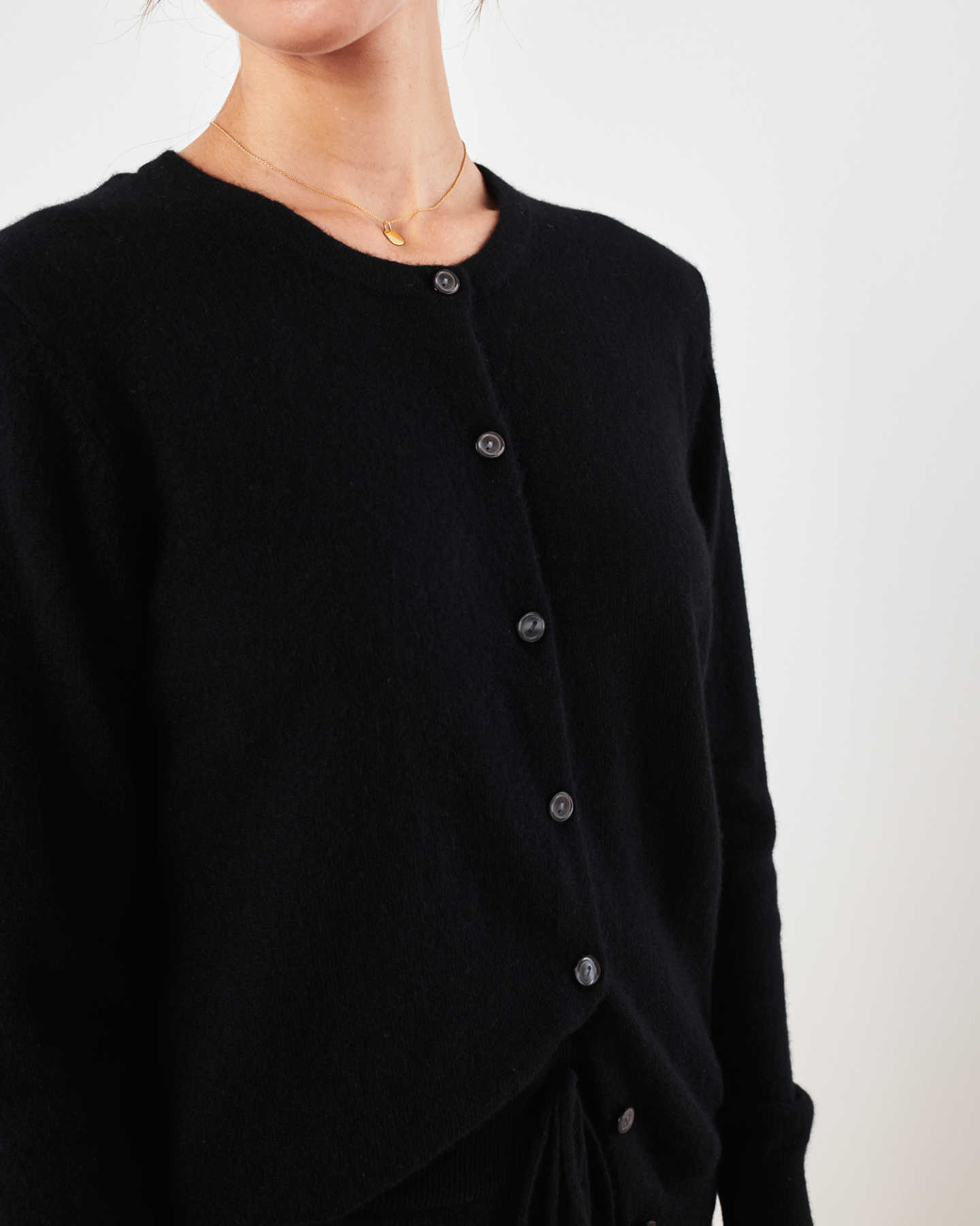 Woman wearing black cashmere cardigan sweater and black cashmere sweatpants zoomed