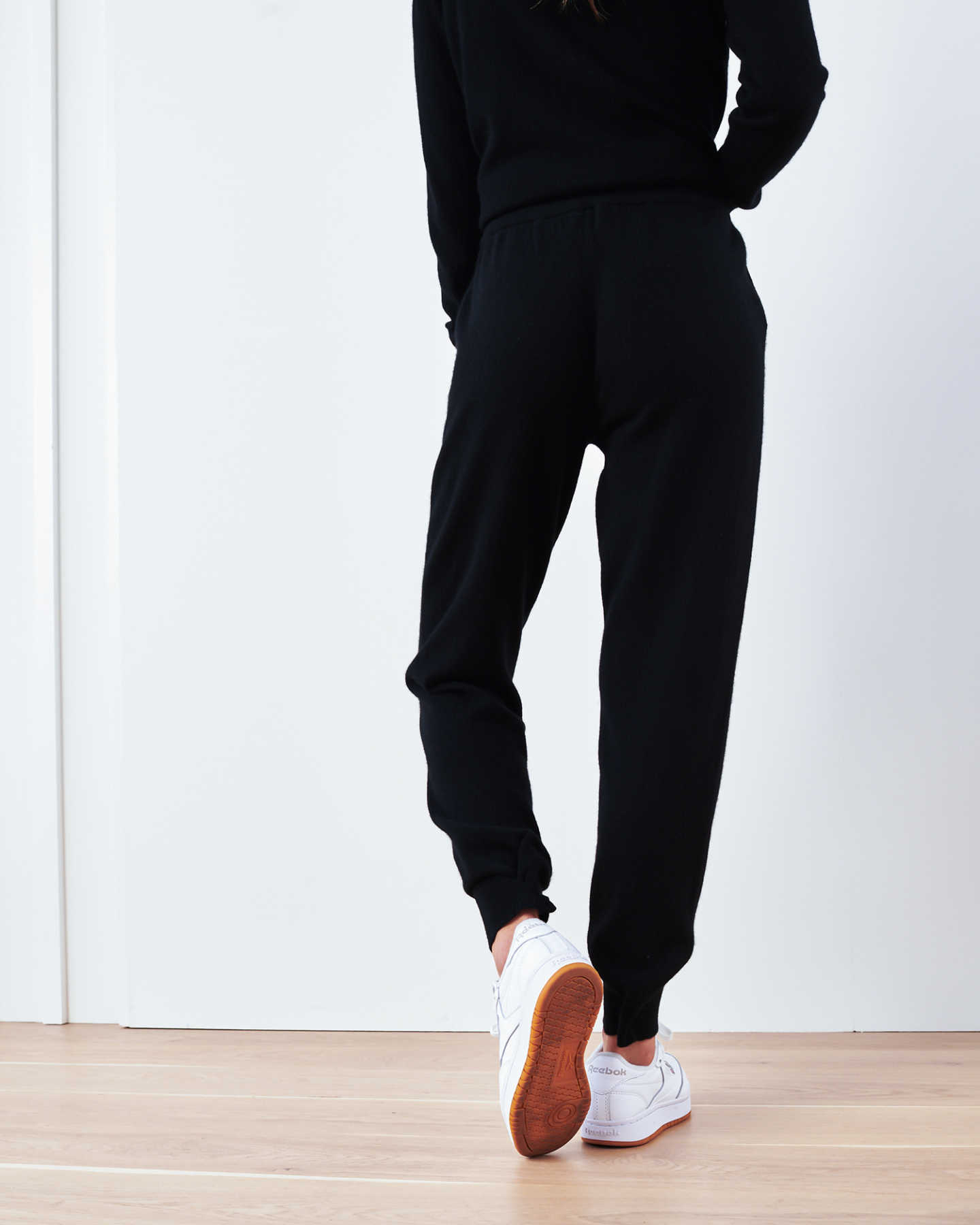 Woman wearing black cashmere sweatpants & cashmere joggers from behind
