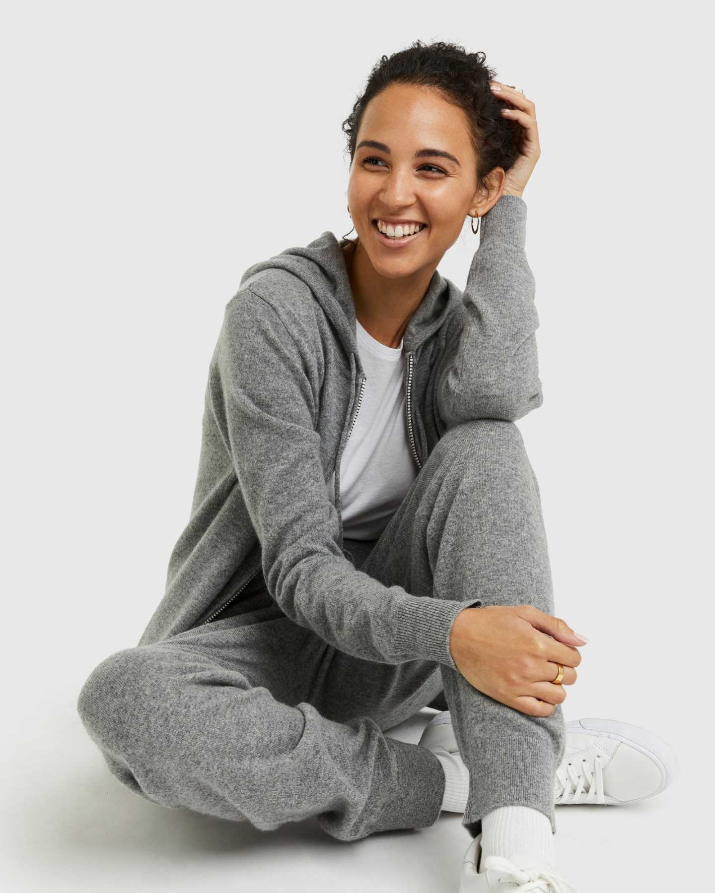Woman wearing grey cashmere zip hoodie and matching cashmere sweatpants