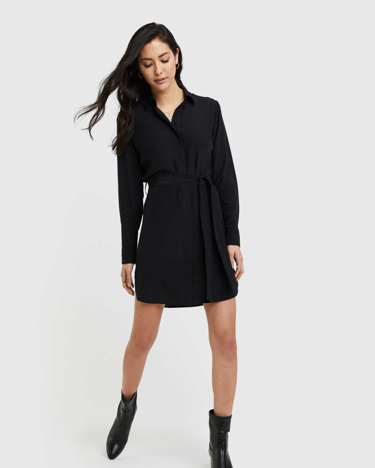 Woman wearing silk shirt dress in black looking down
