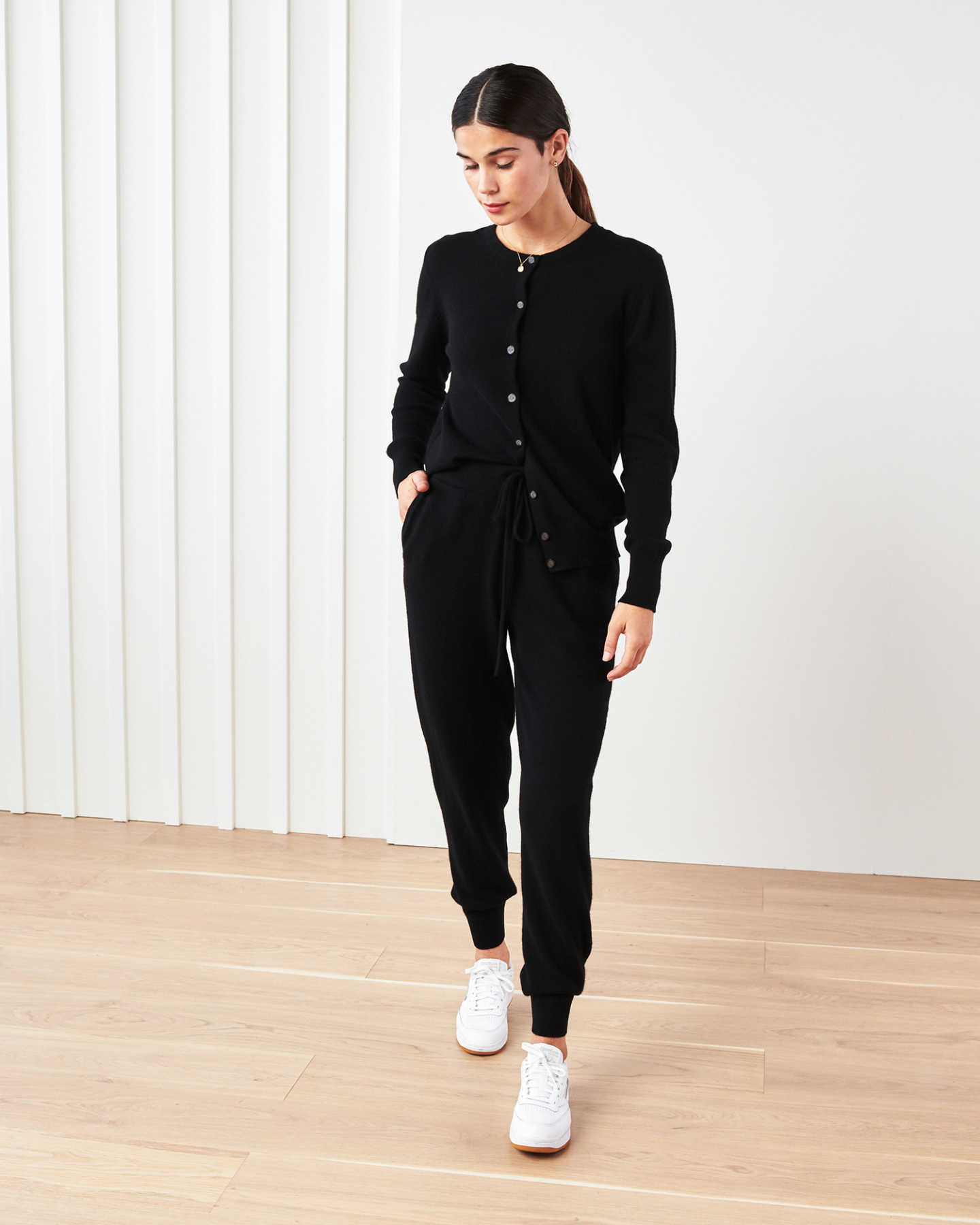 Woman wearing black cashmere cardigan sweater and black cashmere sweatpants striding