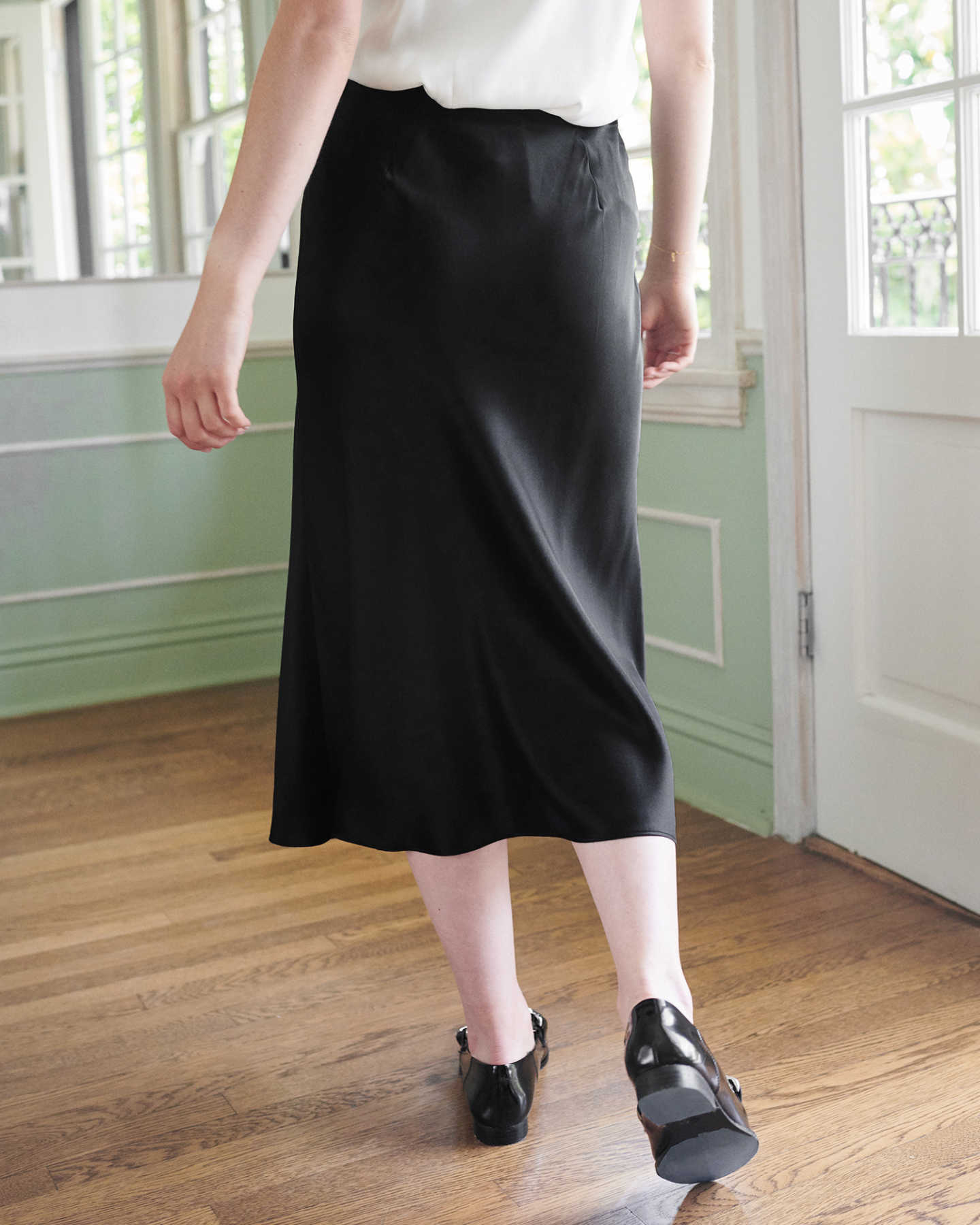 Woman wearing black silk skirt from back