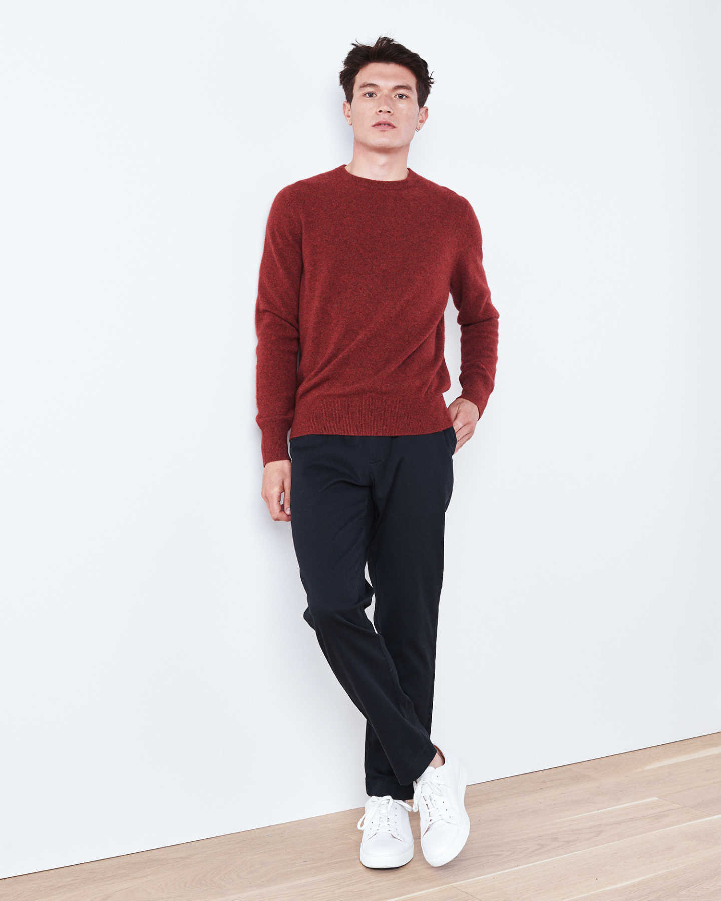 Man wearing red men's cashmere sweater against wall