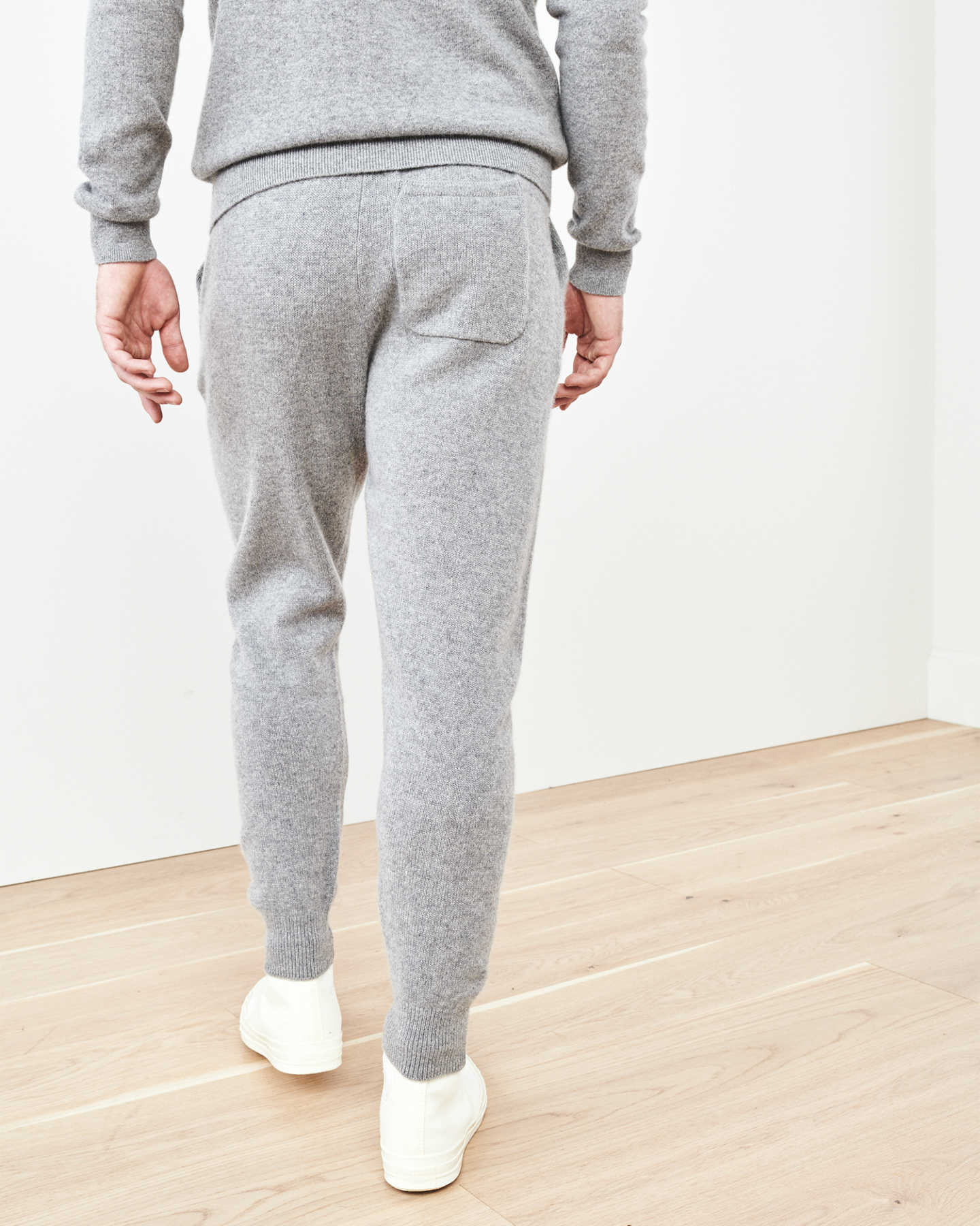 Man wearing cashmere men's cashmere joggers / cashmere sweatpants in grey from back