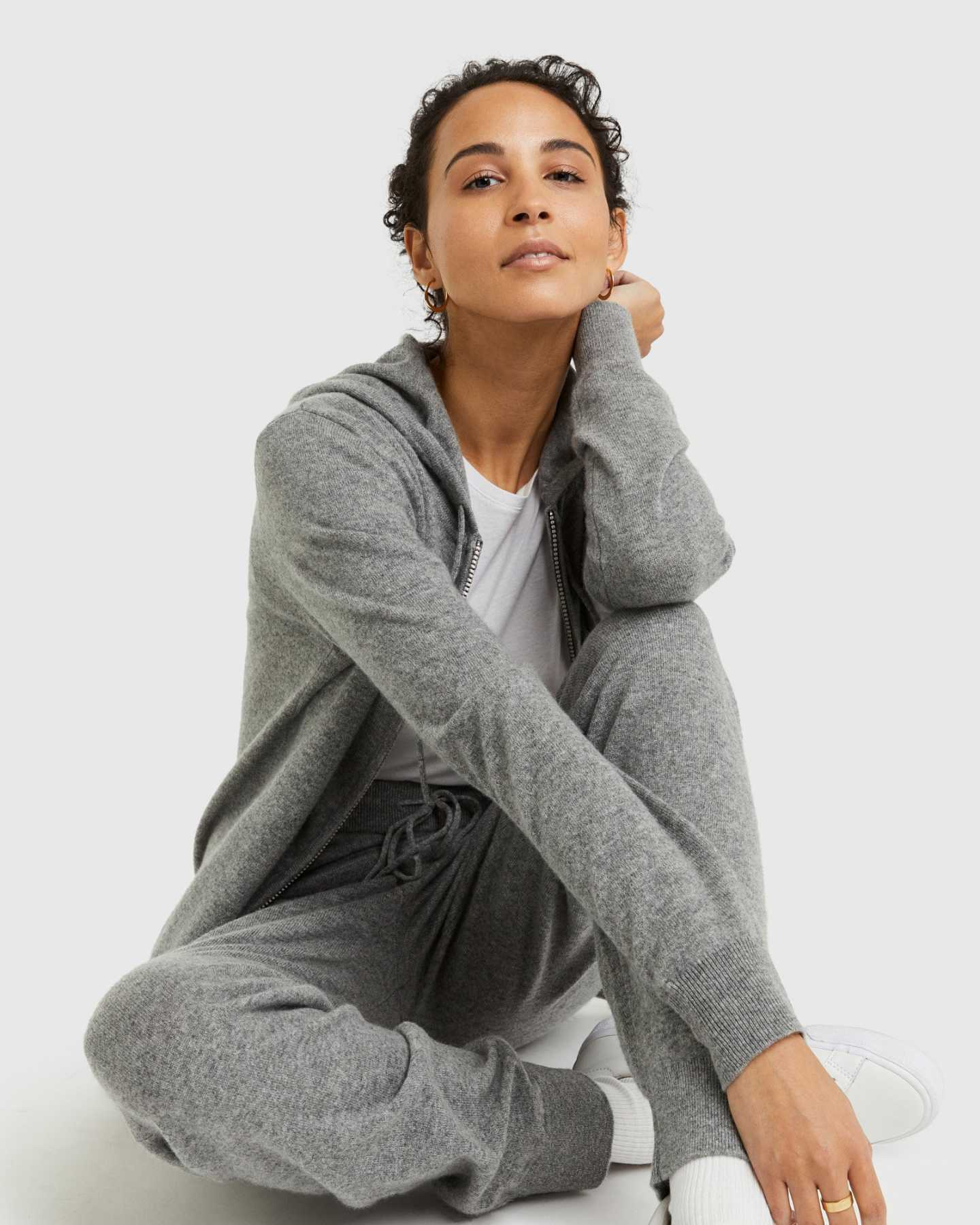 Woman wearing grey cashmere zip hoodie and matching cashmere sweatpants smiling at camera