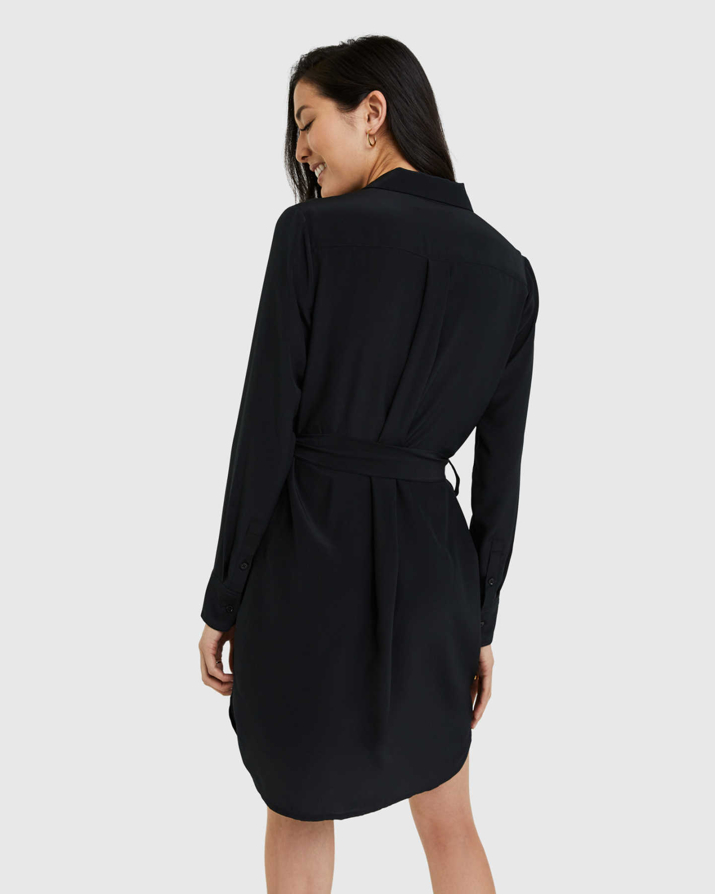 Woman wearing silk shirt dress in black from back