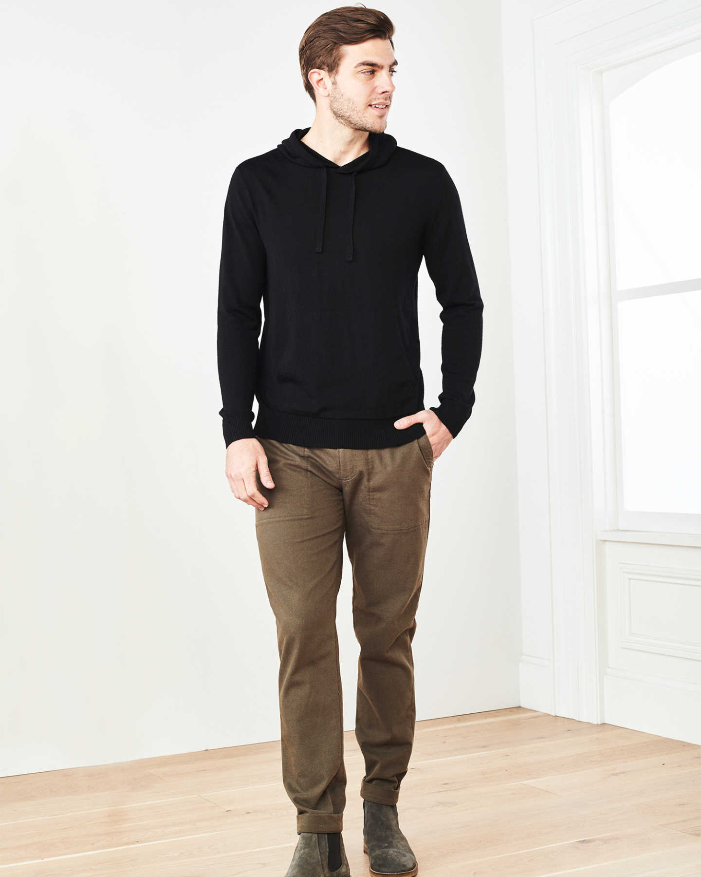 Man wearing merino wool hoodie in black looking left