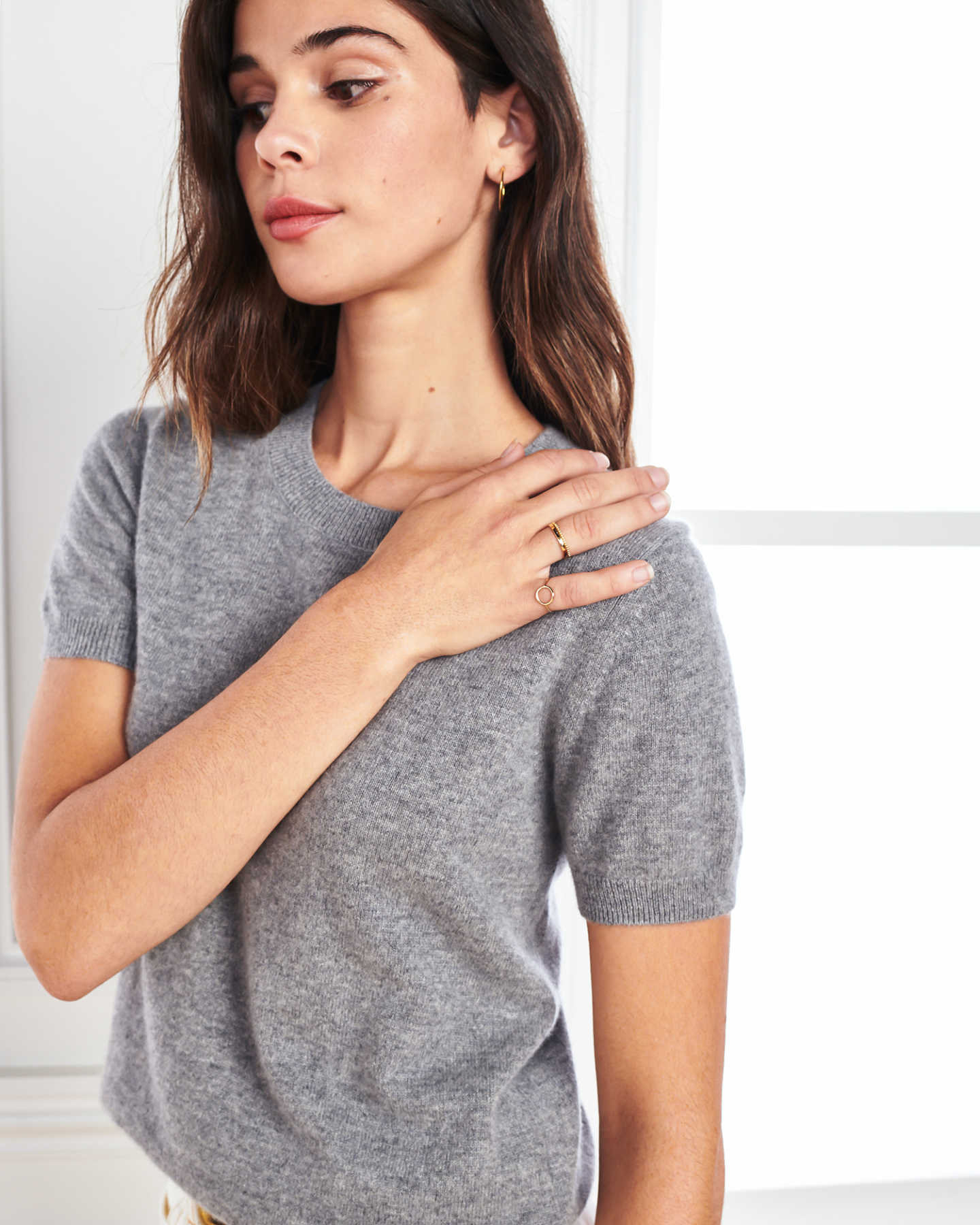 woman wearing grey cashmere tee and short sleeve cashmere sweater hand on shoulder