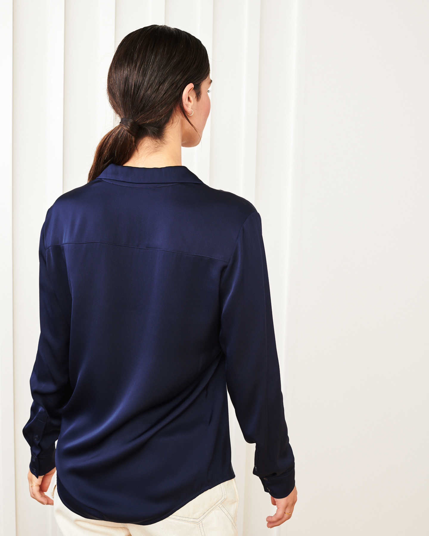 woman wearing silk notch collar blouse in navy from back
