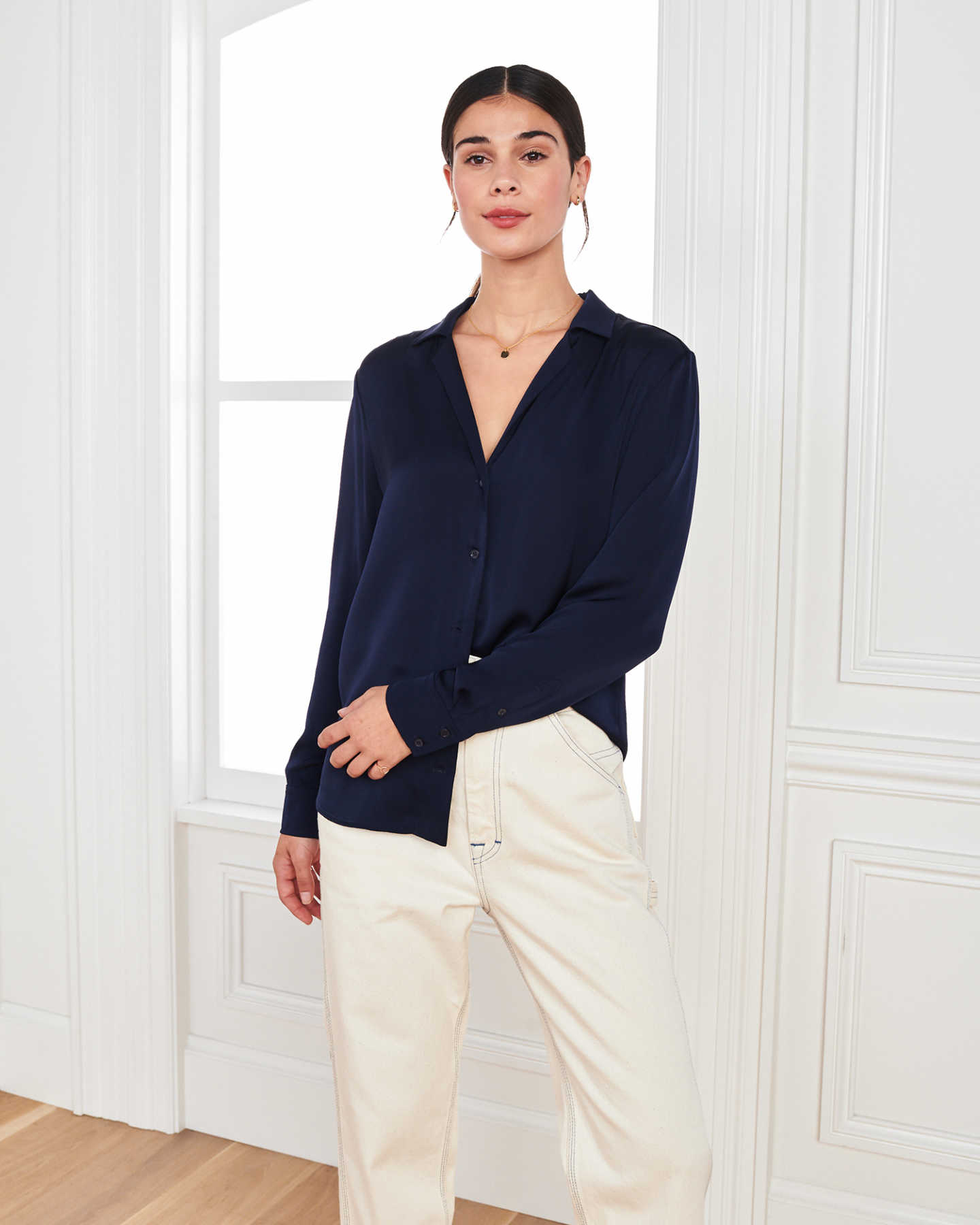 woman wearing silk notch collar blouse in navy by window