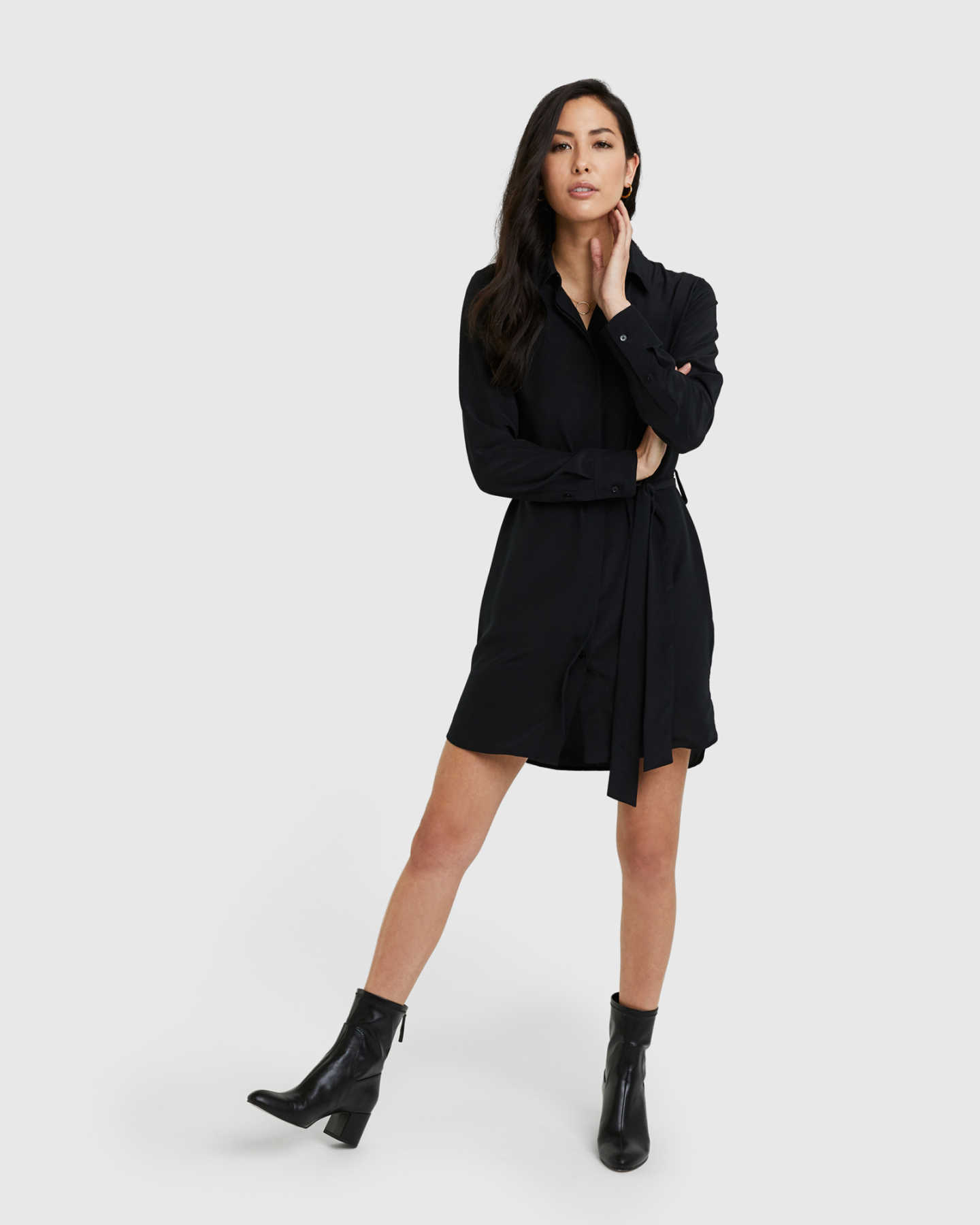 Woman wearing silk shirt dress in black from front