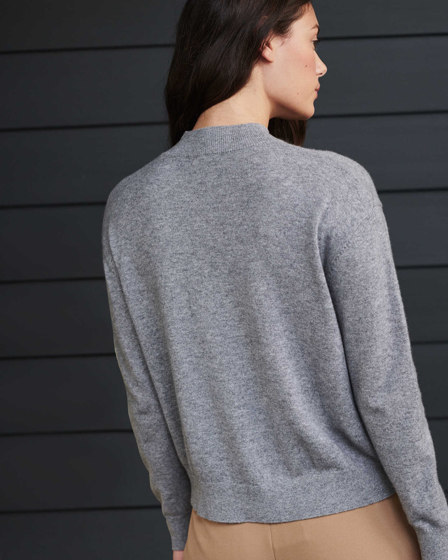 Woman wearing grey cashmere mockneck sweater from back