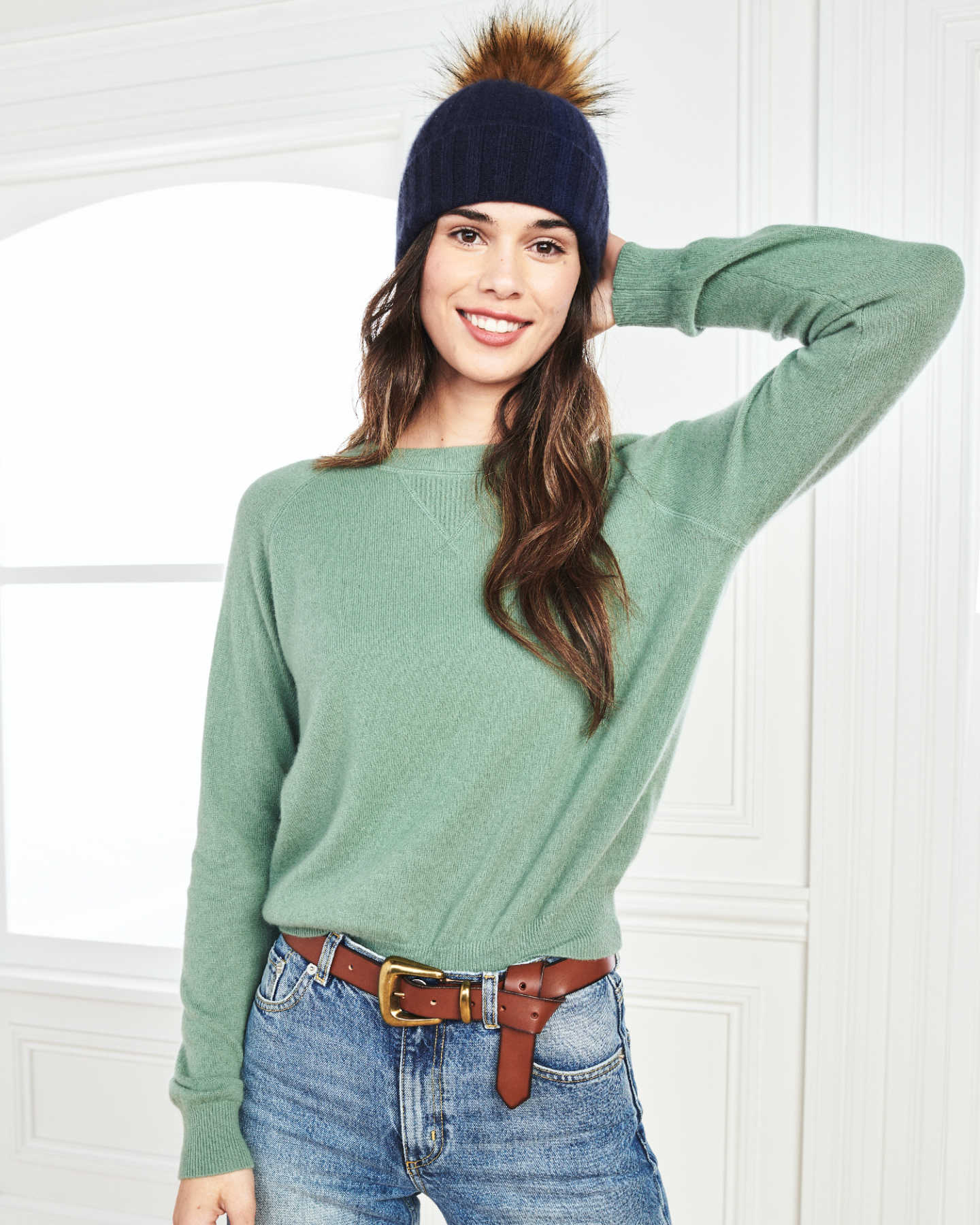 Woman wearing a womens beanie with pom in navy and matching cashmere sweatshirt in green smiling