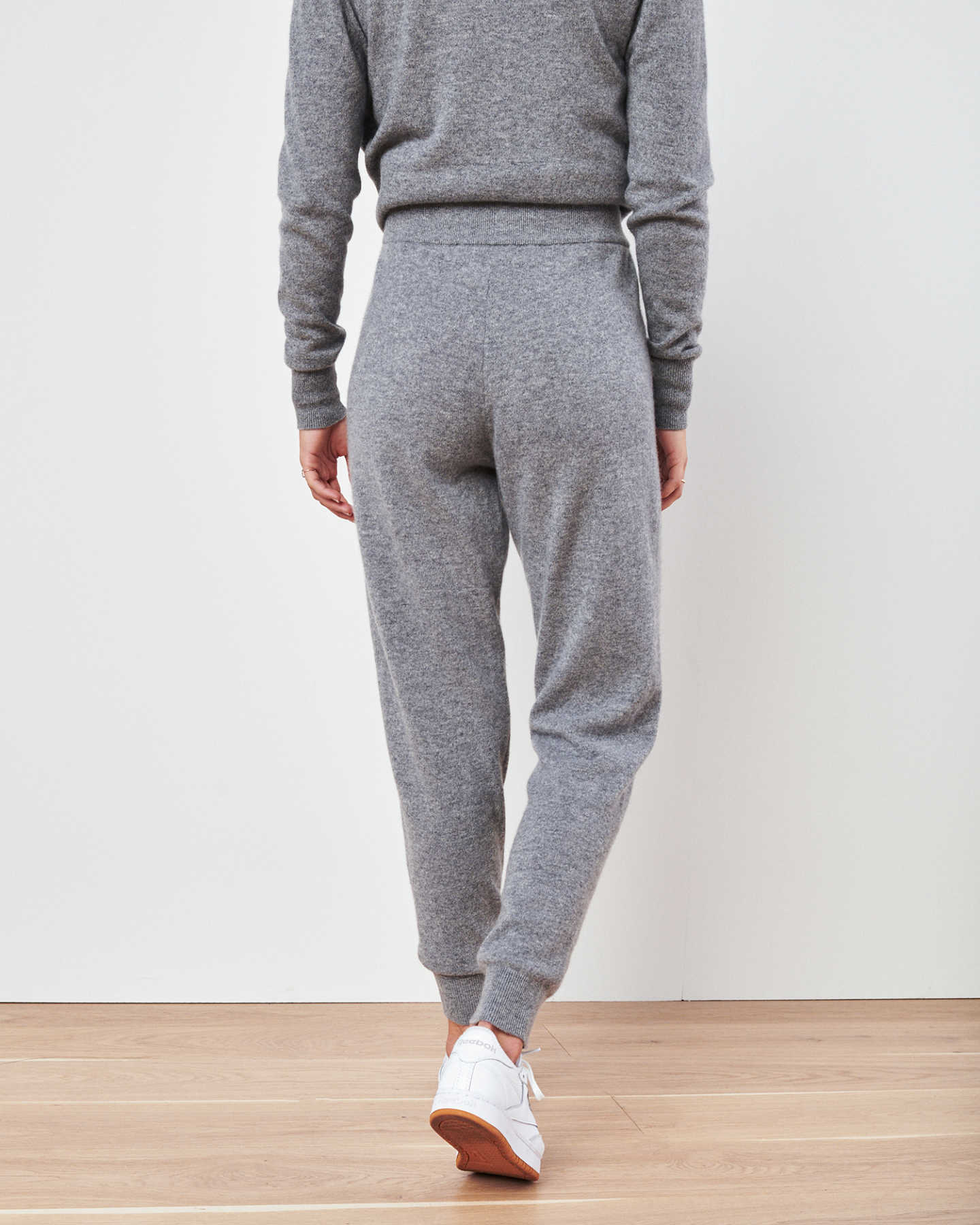 Woman wearing grey cashmere sweatpants & cashmere joggers from behind