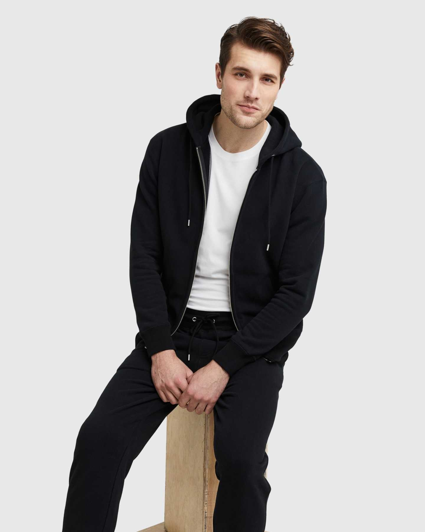 Man wearing 100% organic cotton heavyweight sweatpants in black and matching hoodie