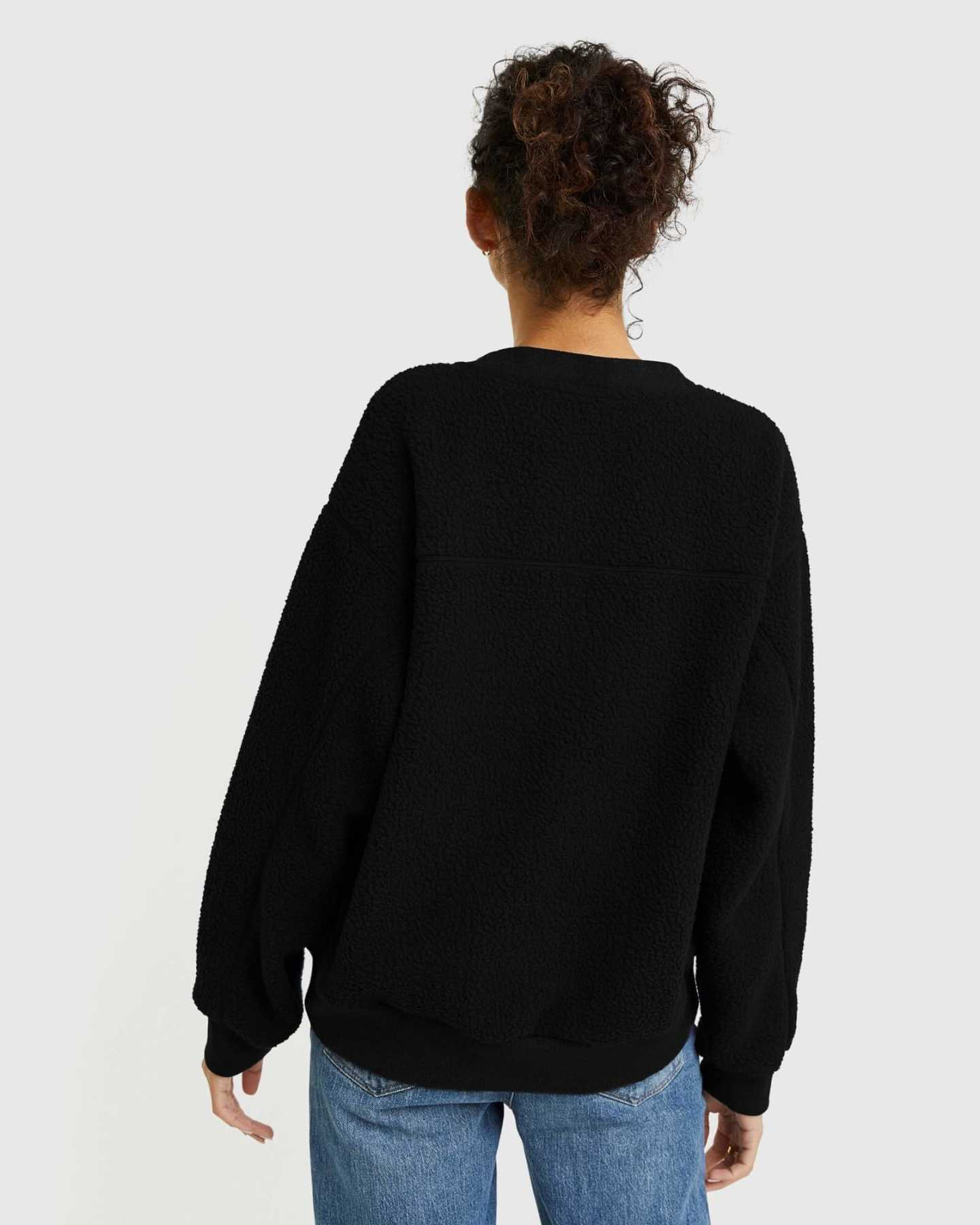 woman wearing sherpa crewneck sweatshirt in black from back