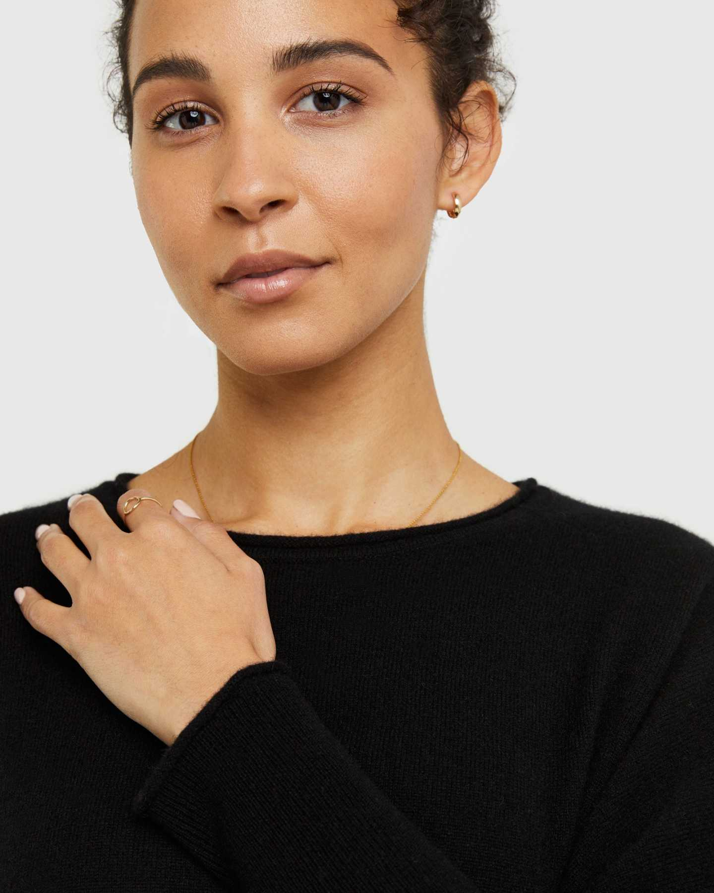 Woman wearing batwing sweater made from cashmere in black up close