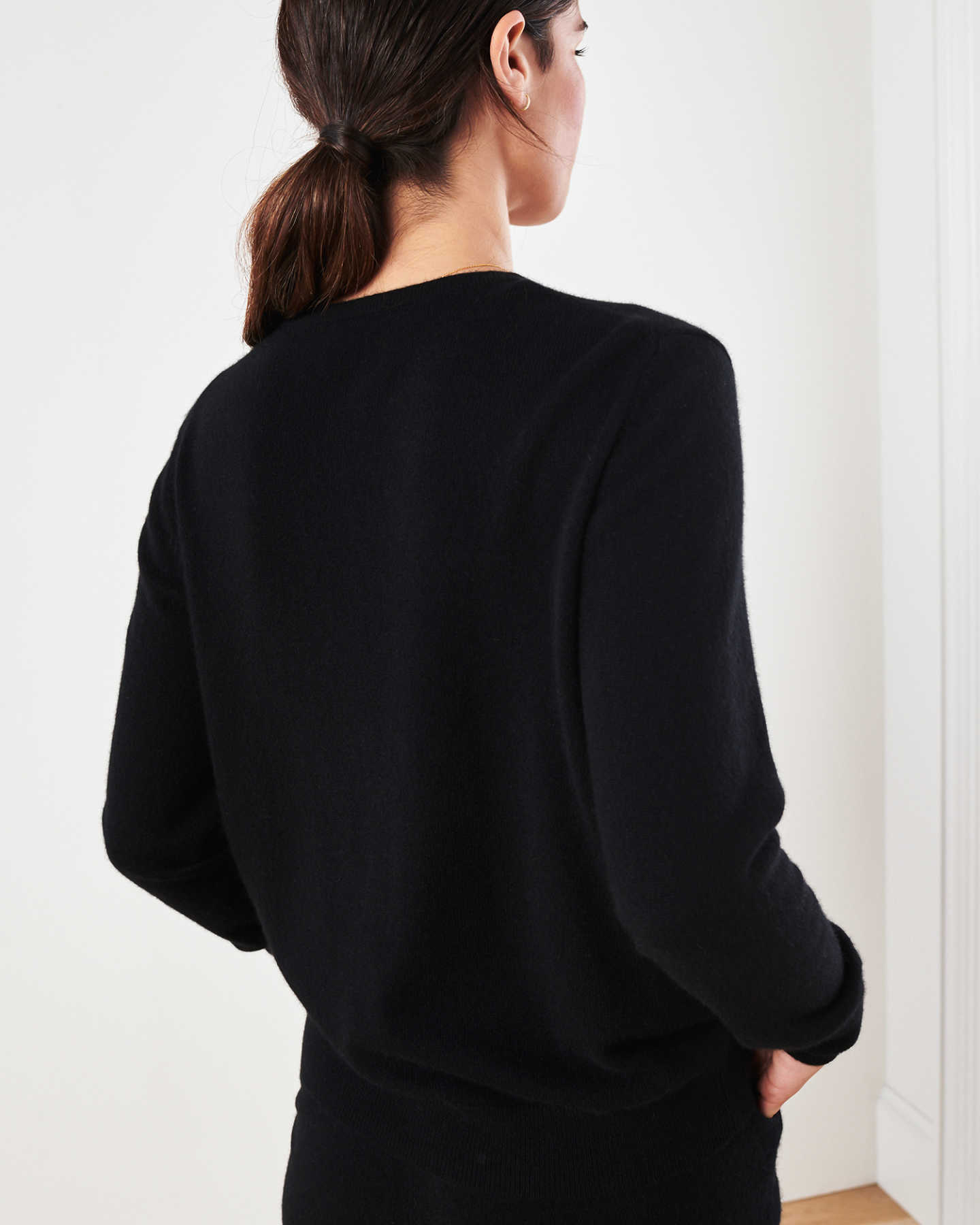 Woman wearing black cashmere cardigan sweater and black cashmere sweatpants behind