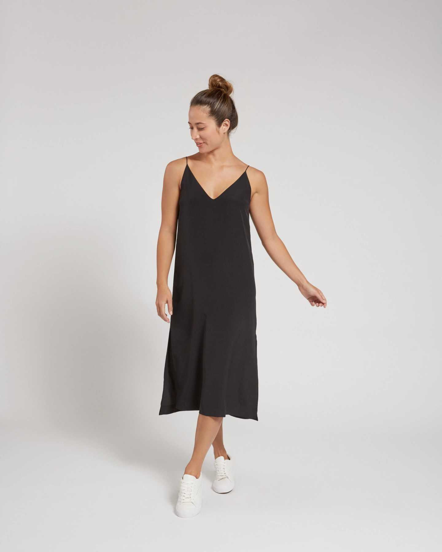 Woman wearing black silk slip dress from front