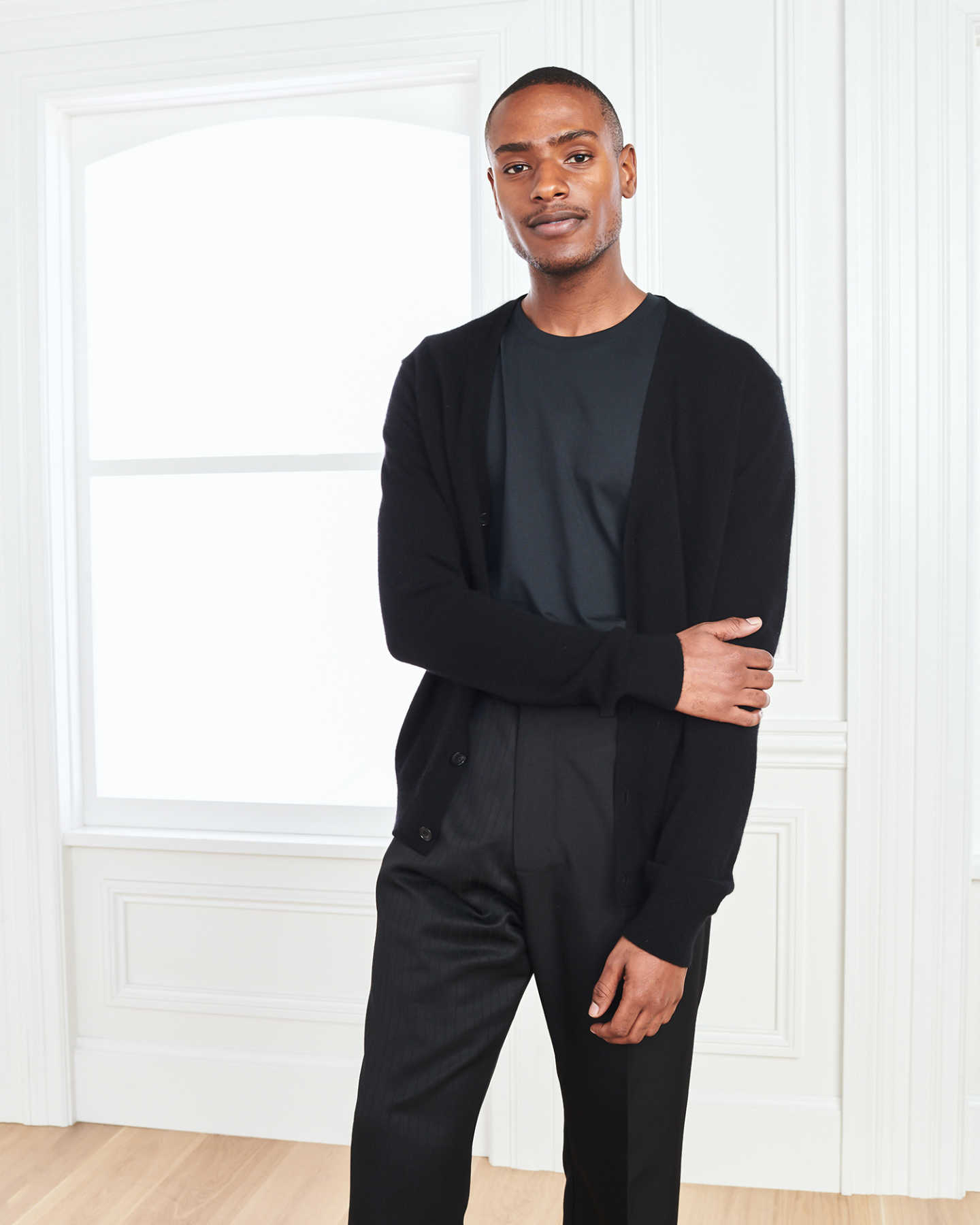 Men's cashmere cardigan sweater in black with arms crossed