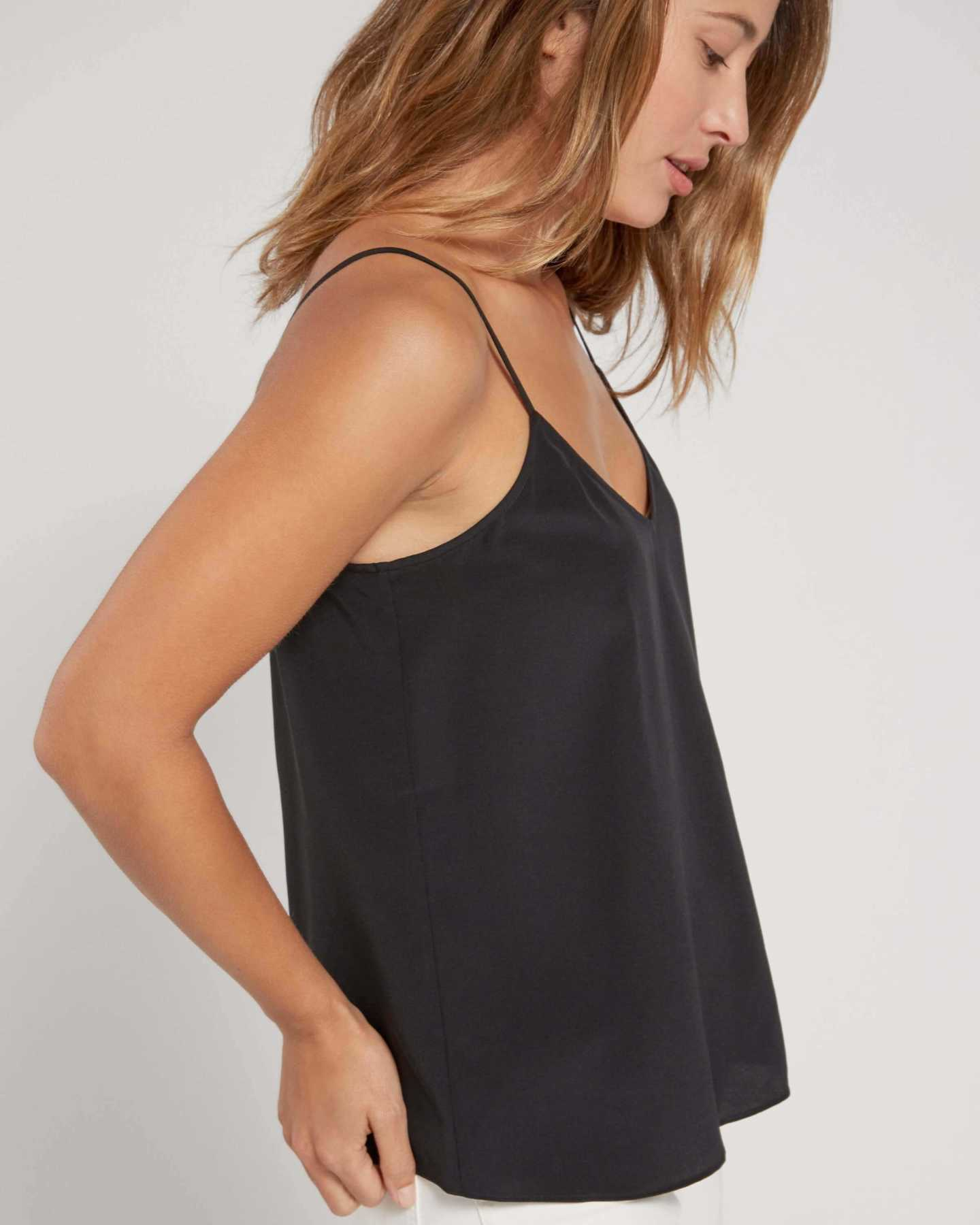 Woman wearing black silk camisole from side